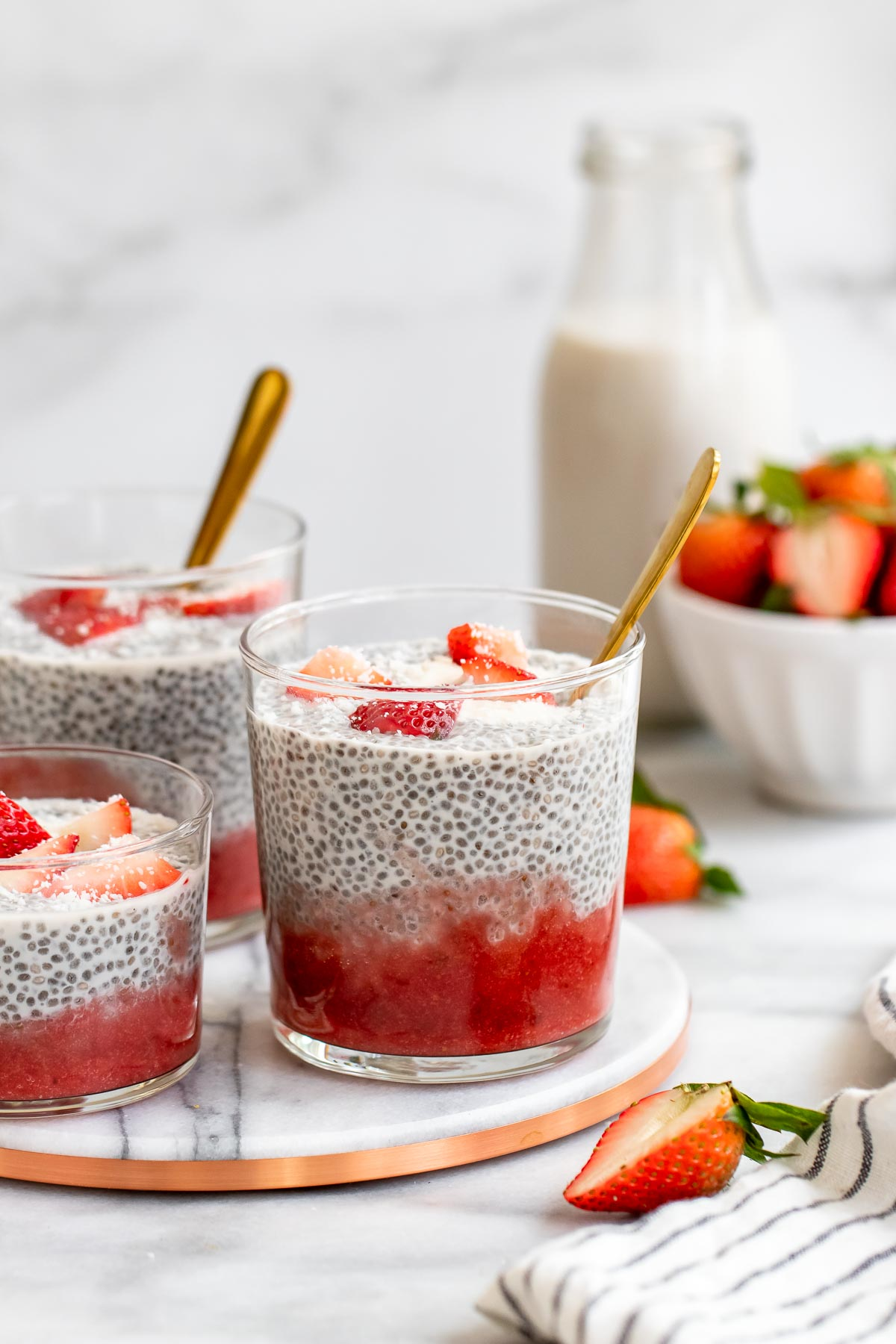 Three jars with the coconut chia pudding and strawberry puree.