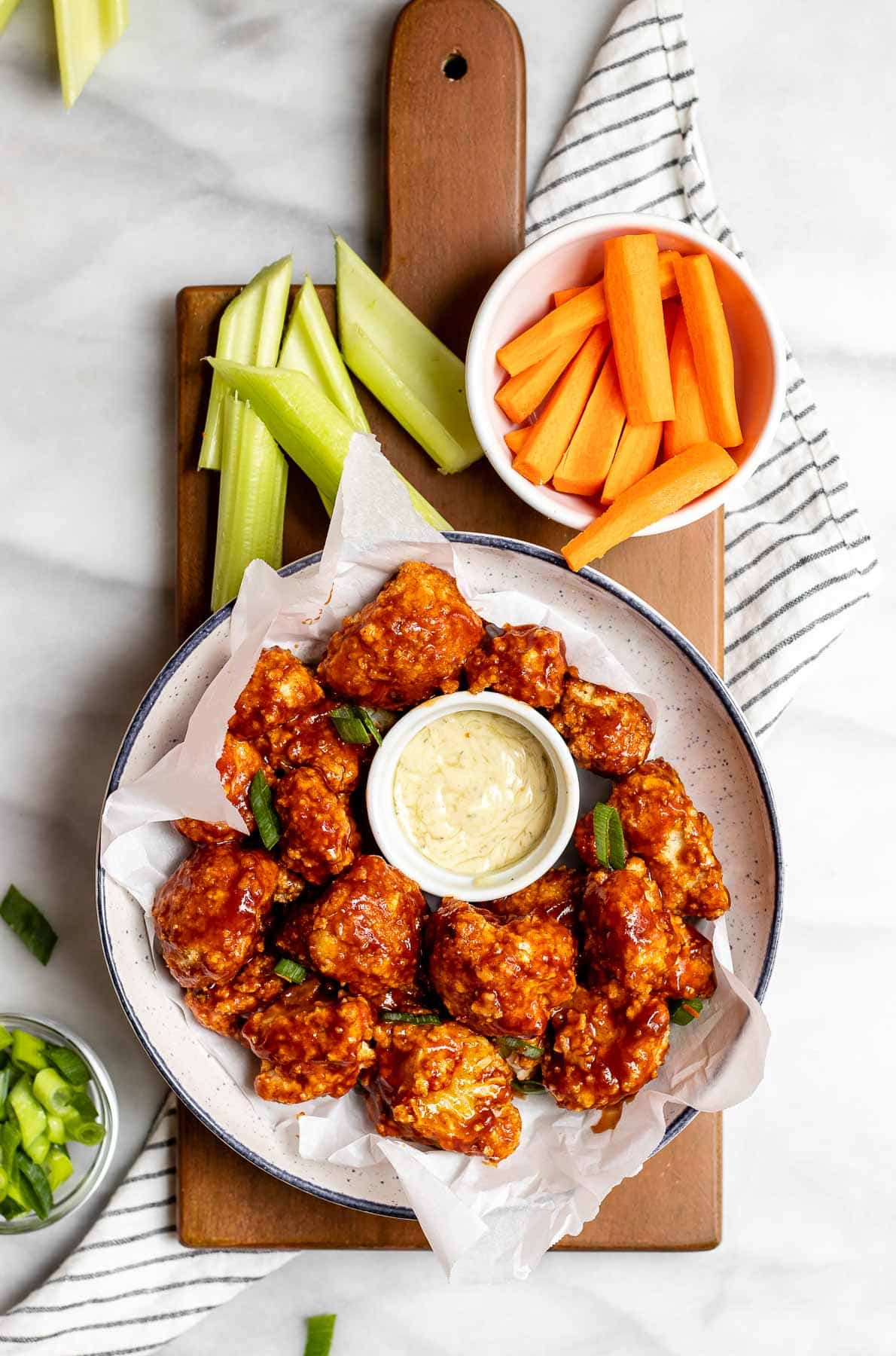 BBQ cauliflower in a bowl with chopped carrots and celery.