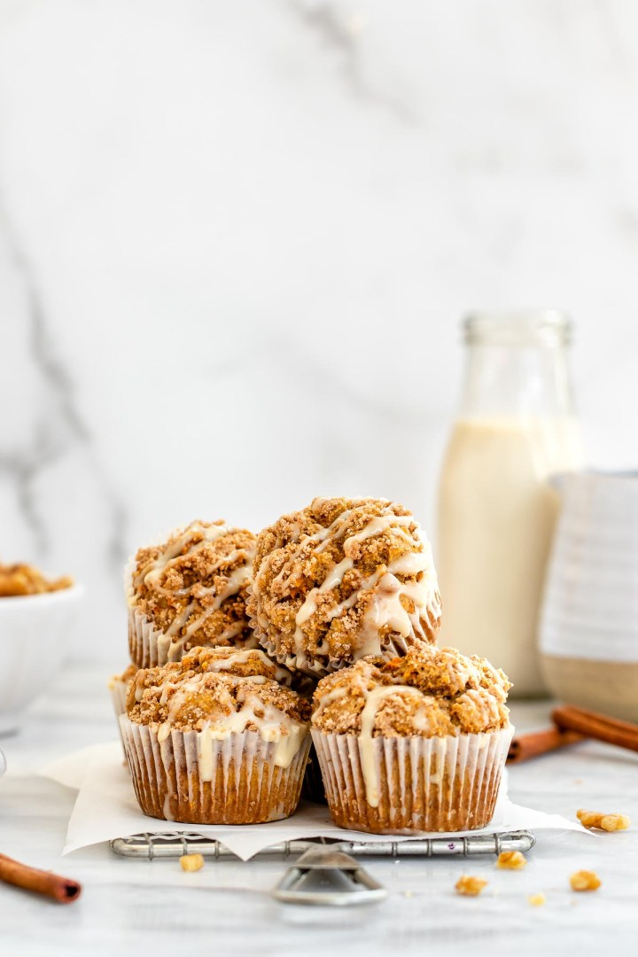 Carrot cake muffins stacked on each other with milk in the background.