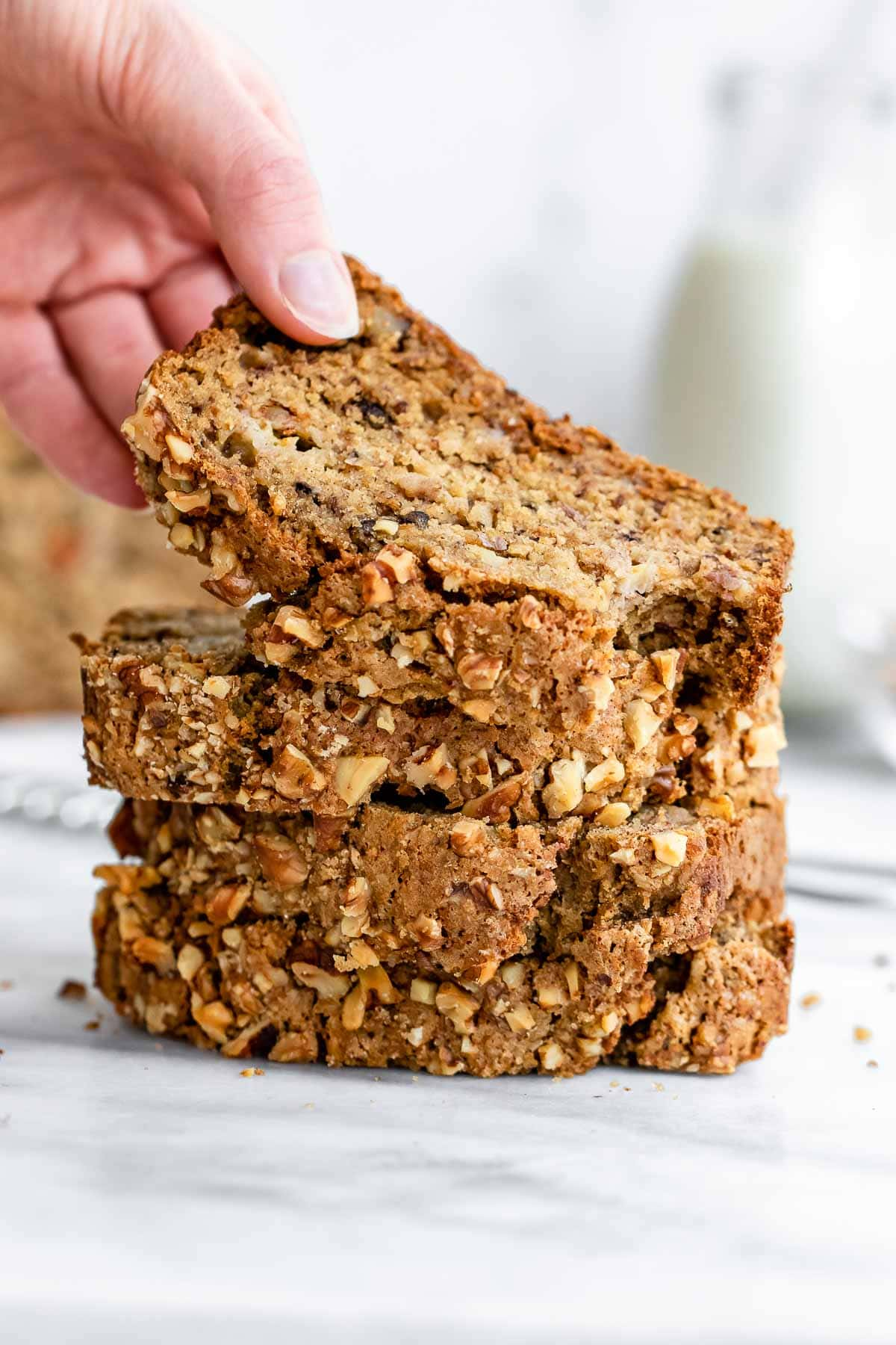 Stack of banana bread slices with a hand picking a top one.