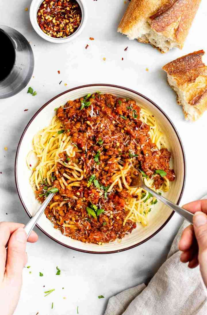 Two hands twirling together the spaghetti with lentil bolognese on top.