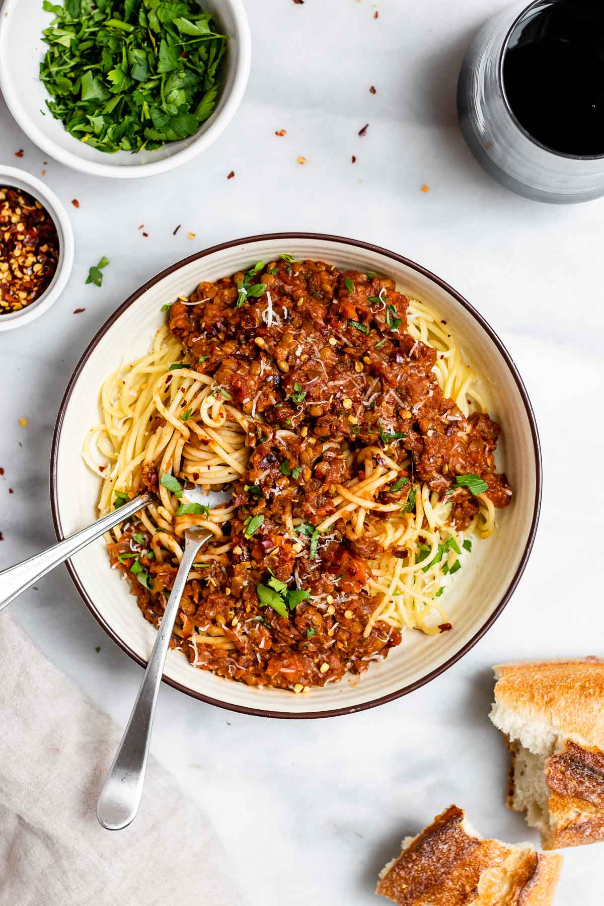 Vegan lentil bolognese in a white bowl with wine and bread on the side.