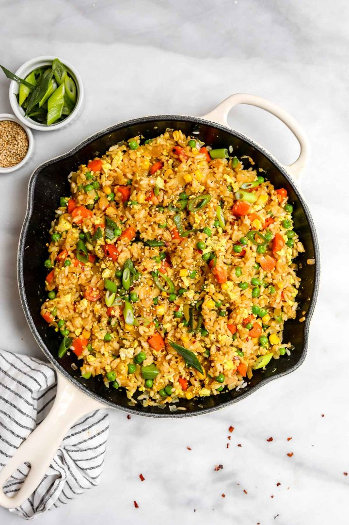 Big skillet with fried rice with soy sauce and sesame seeds on the side.