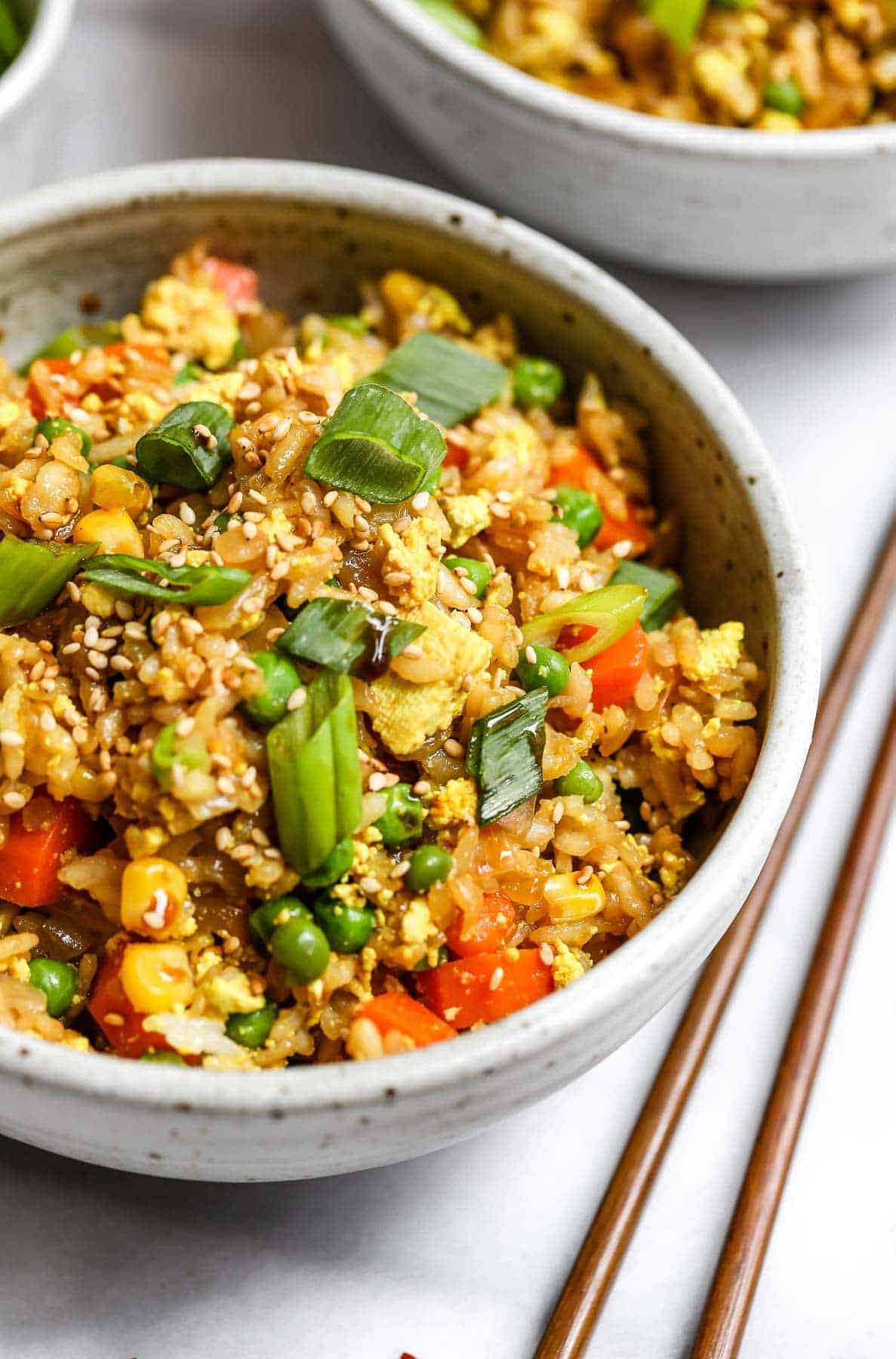 Angled view of vegan fried rice with chopped scallions on top.