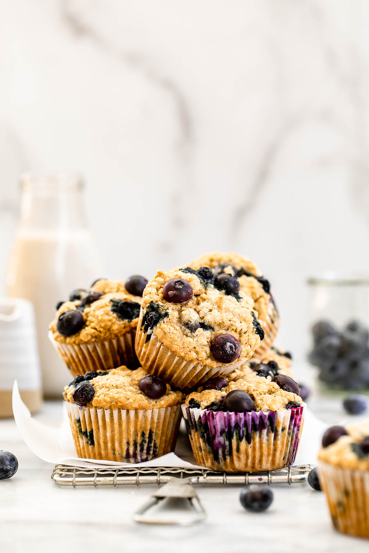 Vegan oatmeal muffins stacked on each other with milk in the background.