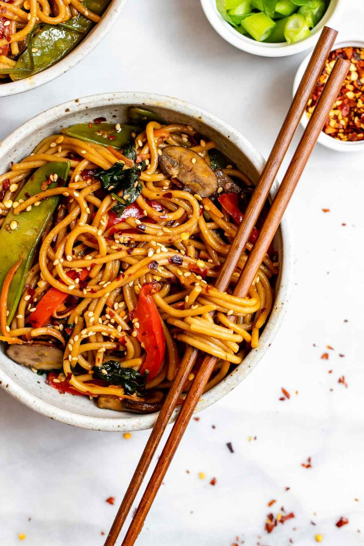 Overhead shot of vegetable lo mein with chopsticks sitting through the noodles.