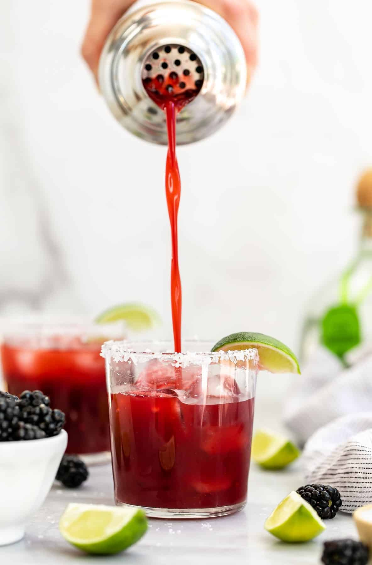 Pouring the blackberry margarita over ice in a glass.
