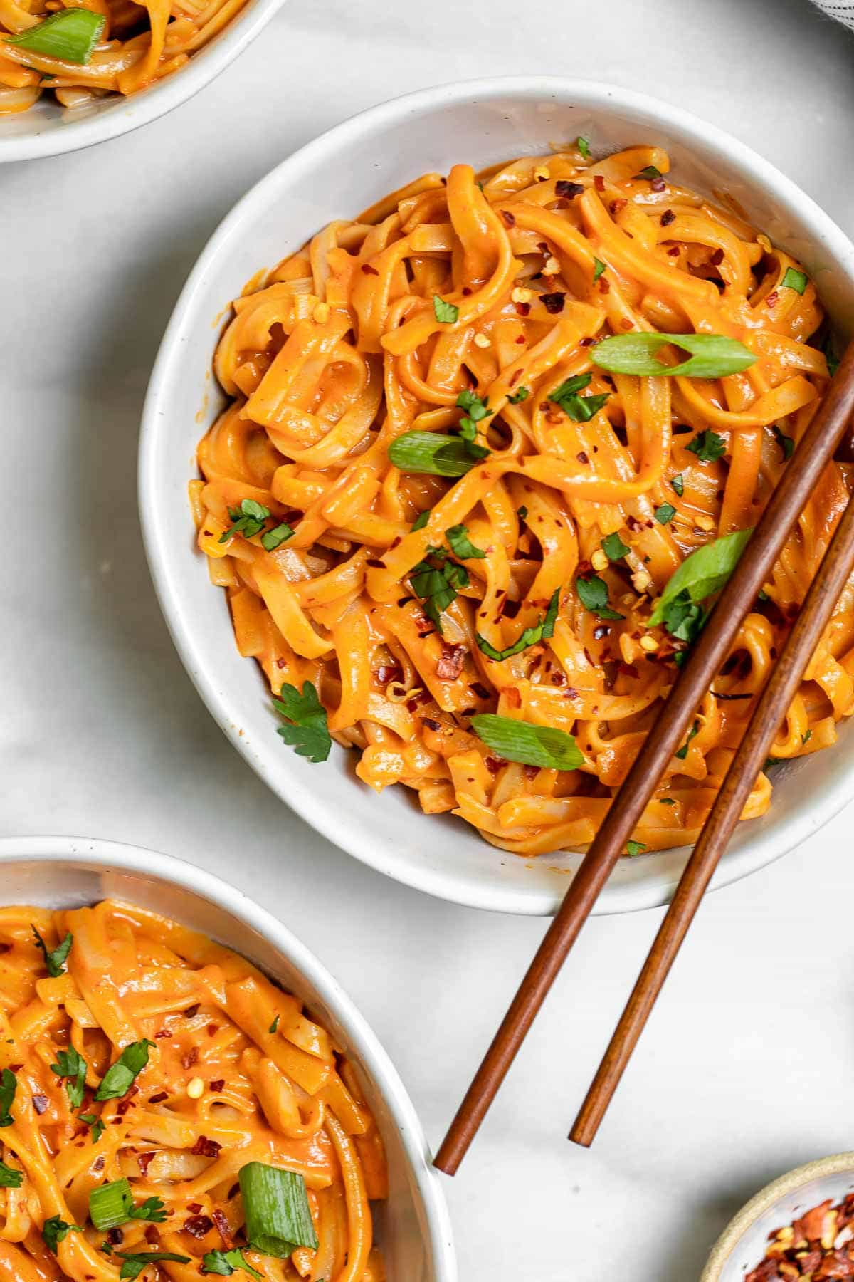 Overhead image of the red curry noodles with red pepper flakes on top.