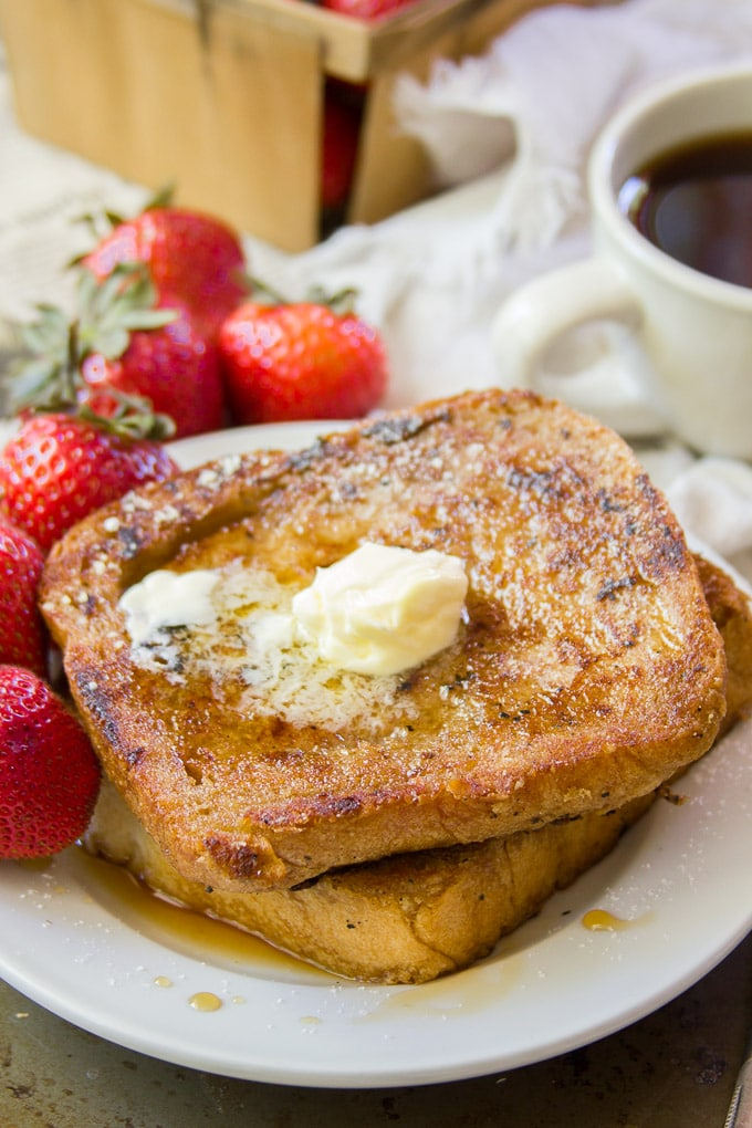 Two pieces of french toast with strawberries.