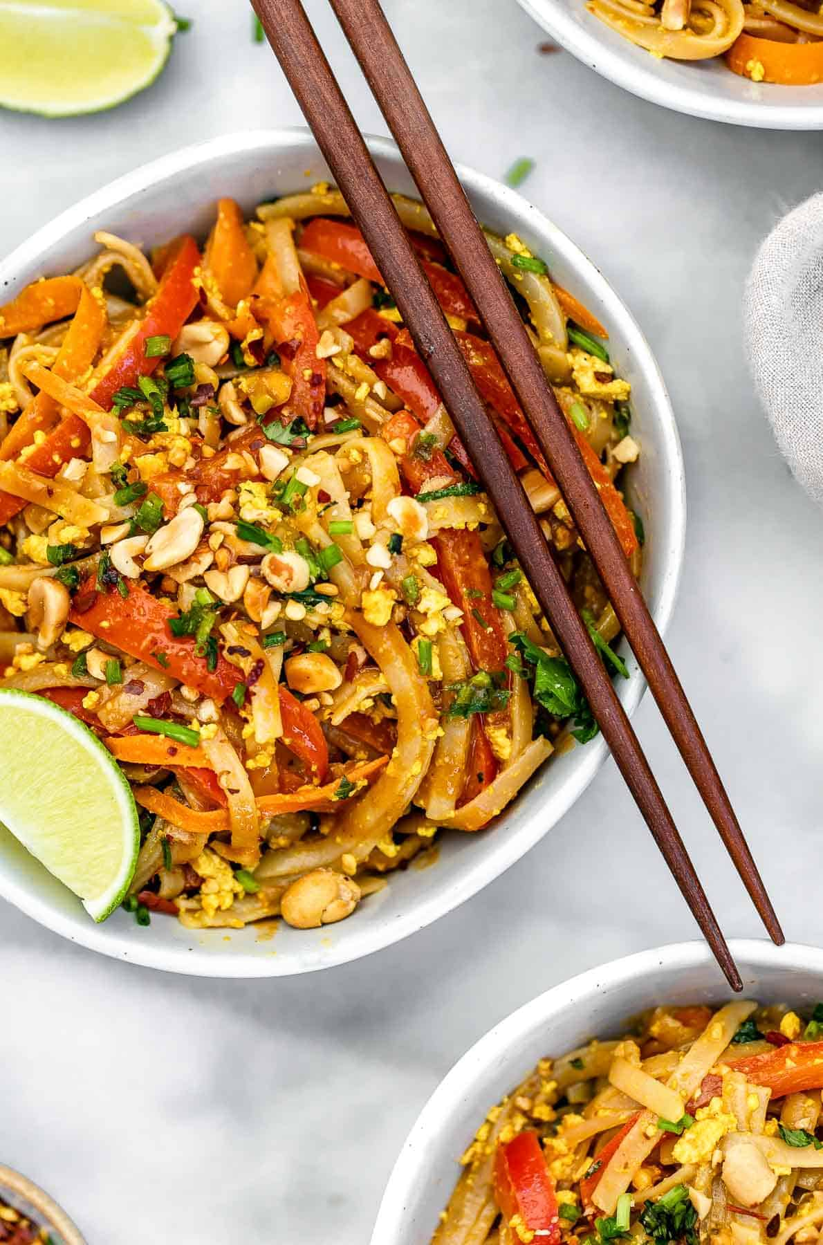 Final pad thai in a bowl with chopsticks and peanuts.