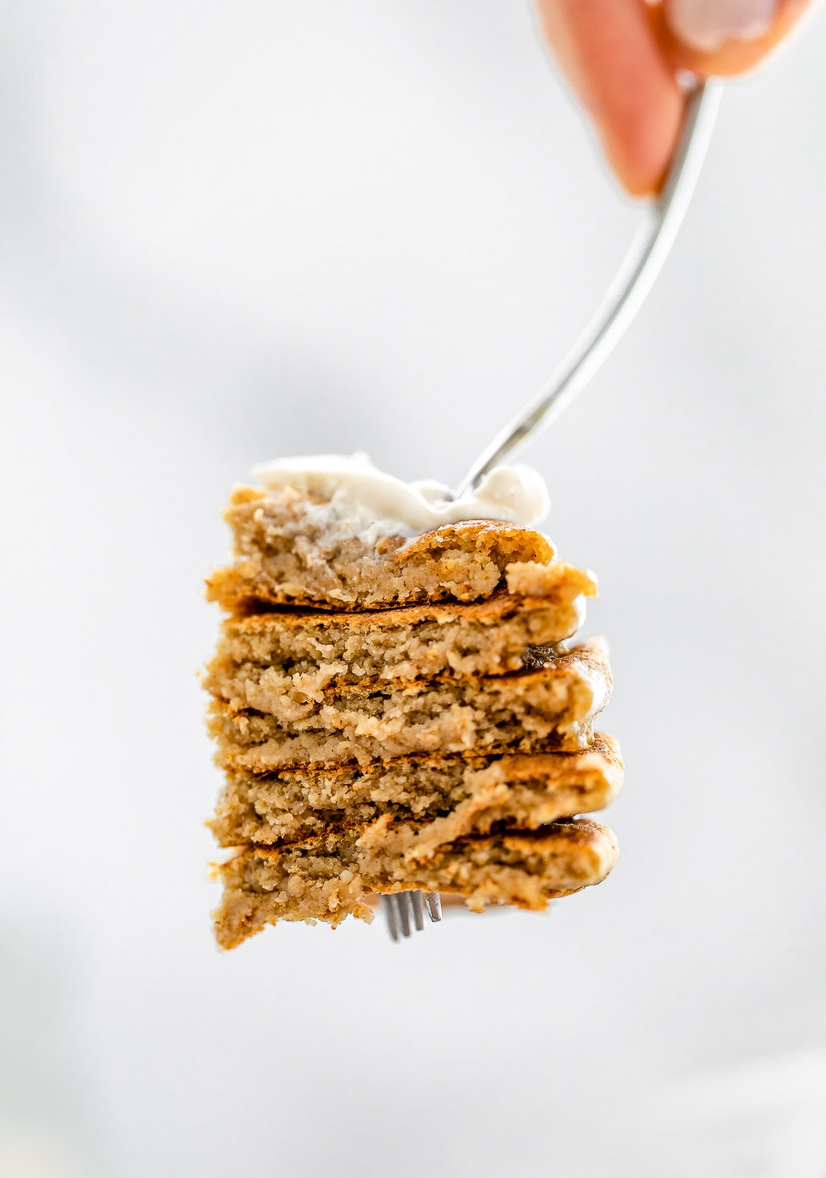 Fork holding up a bite of the vegan gluten free pancakes.