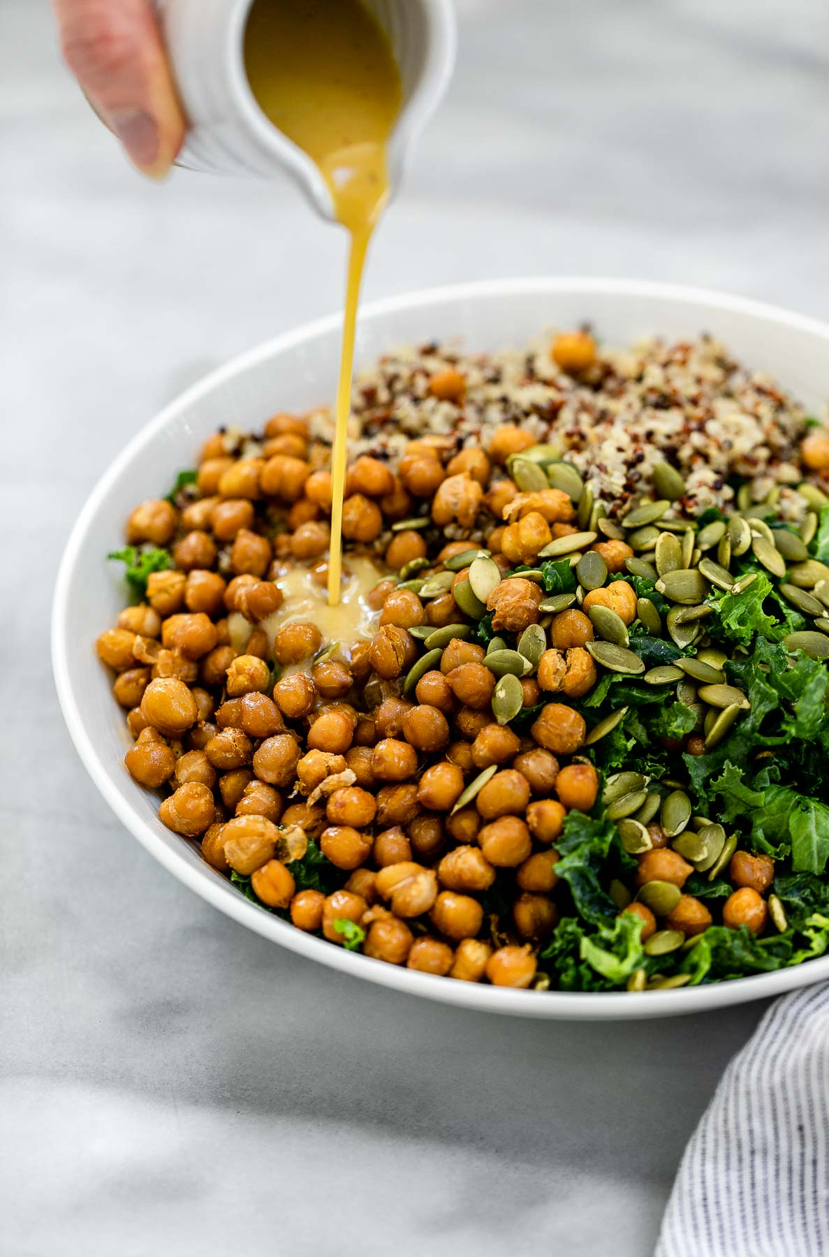 Ingredients for the kale quinoa salad in a bowl with the dressing pouring on top.