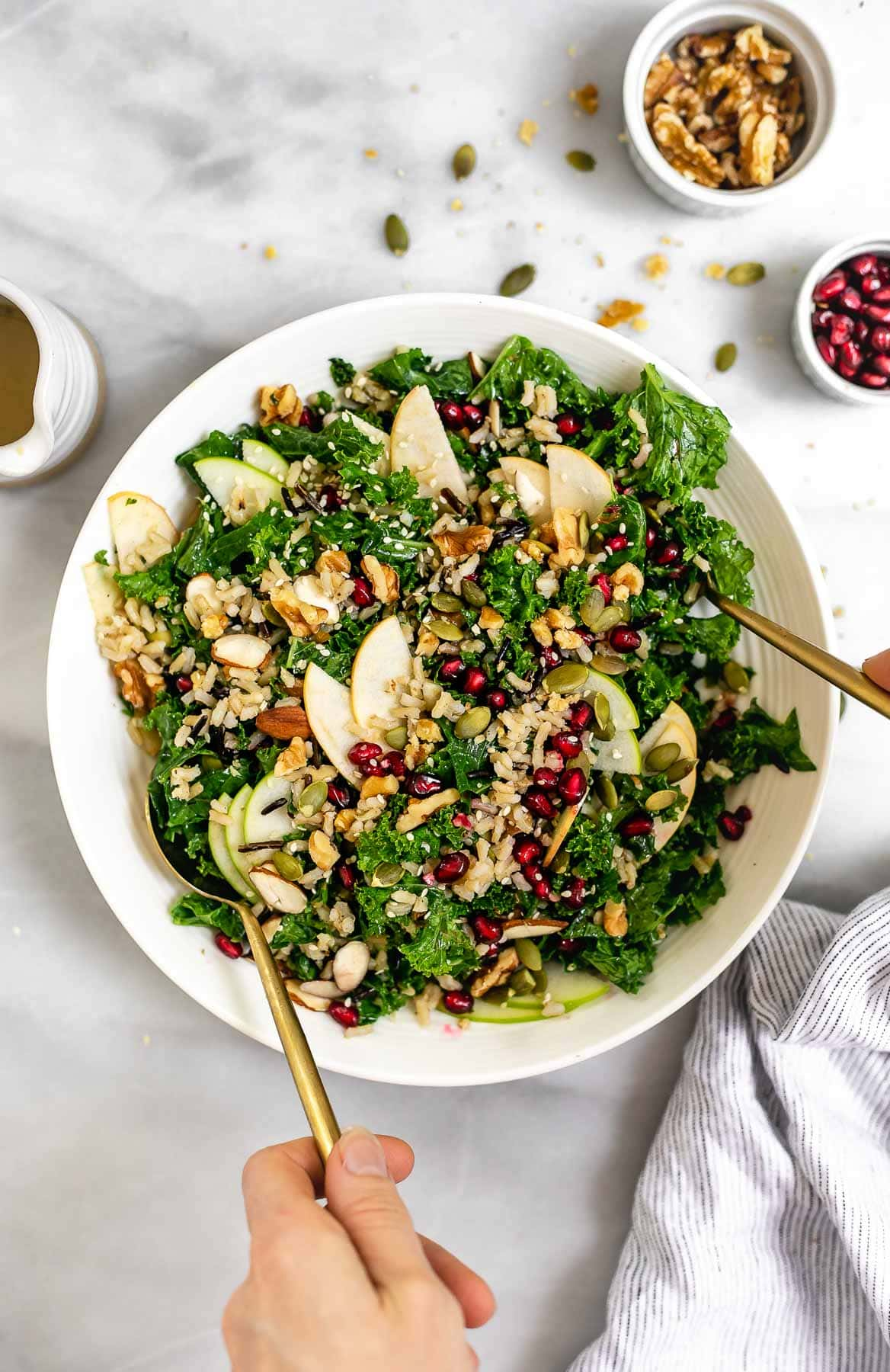 Tossing the apple and kale salad with two gold spoons.