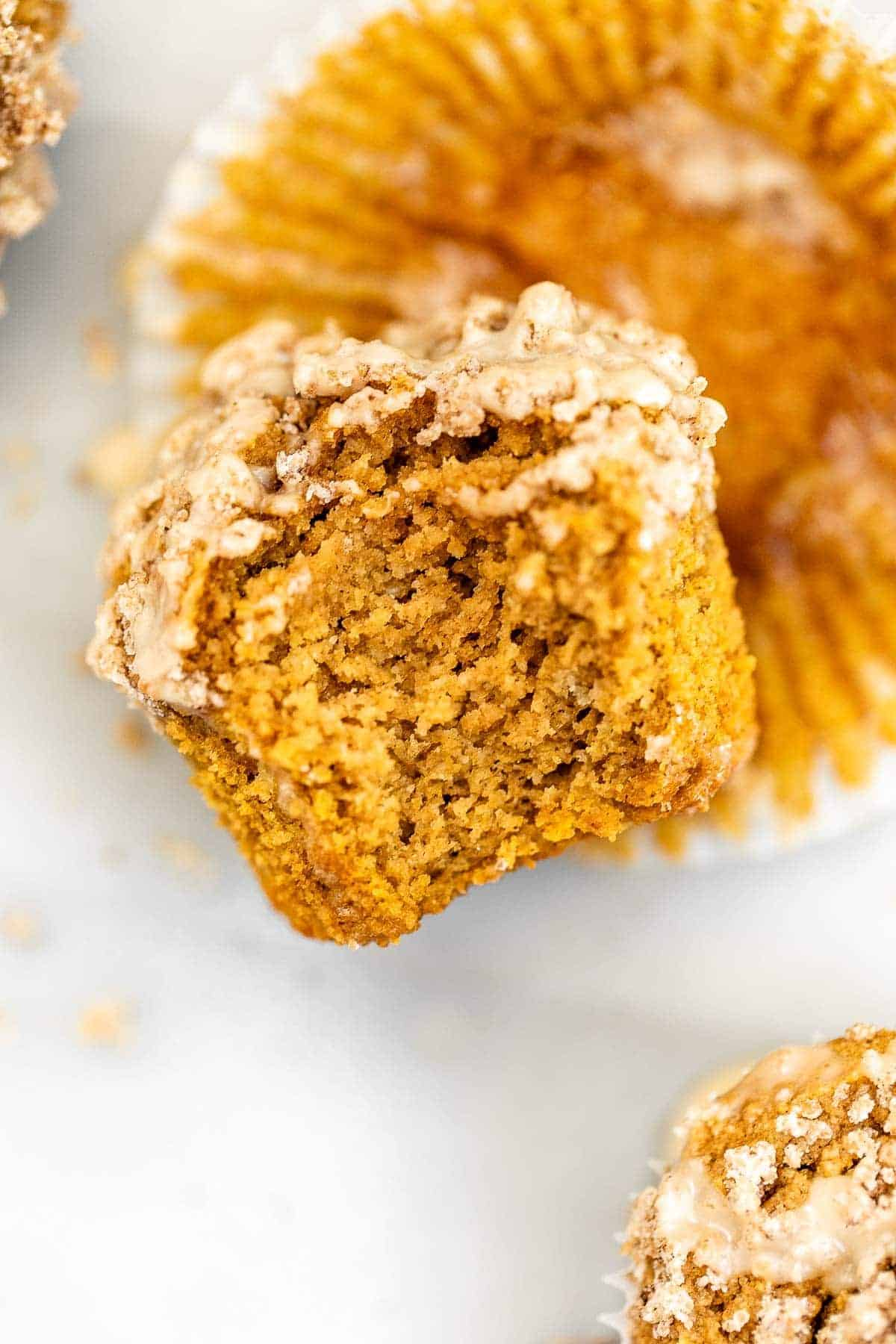Up close shot of a sweet potato muffin with a bite taken out.