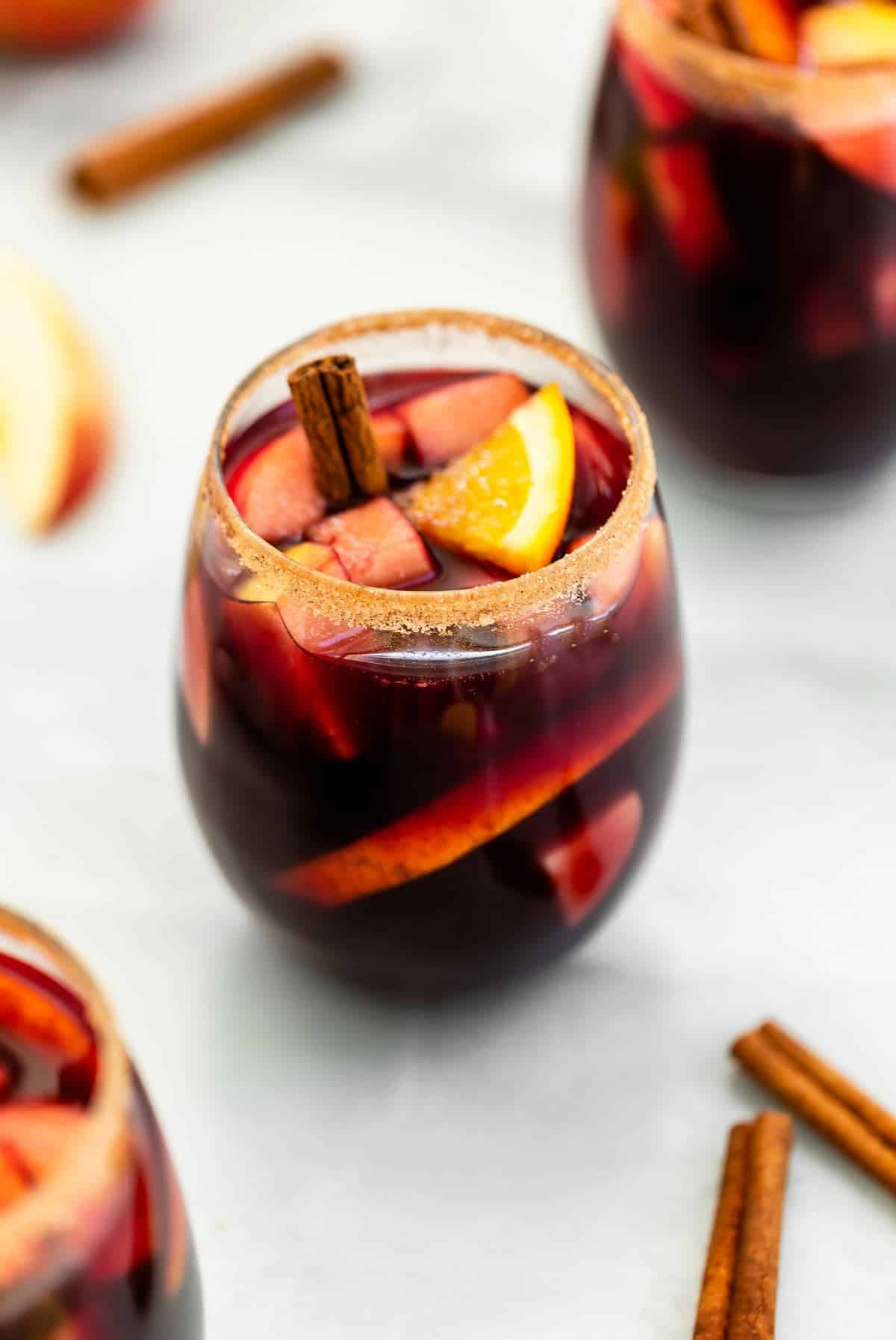 Apple cider sangria with a cinnamon sugar rim in a stemless wine glass.