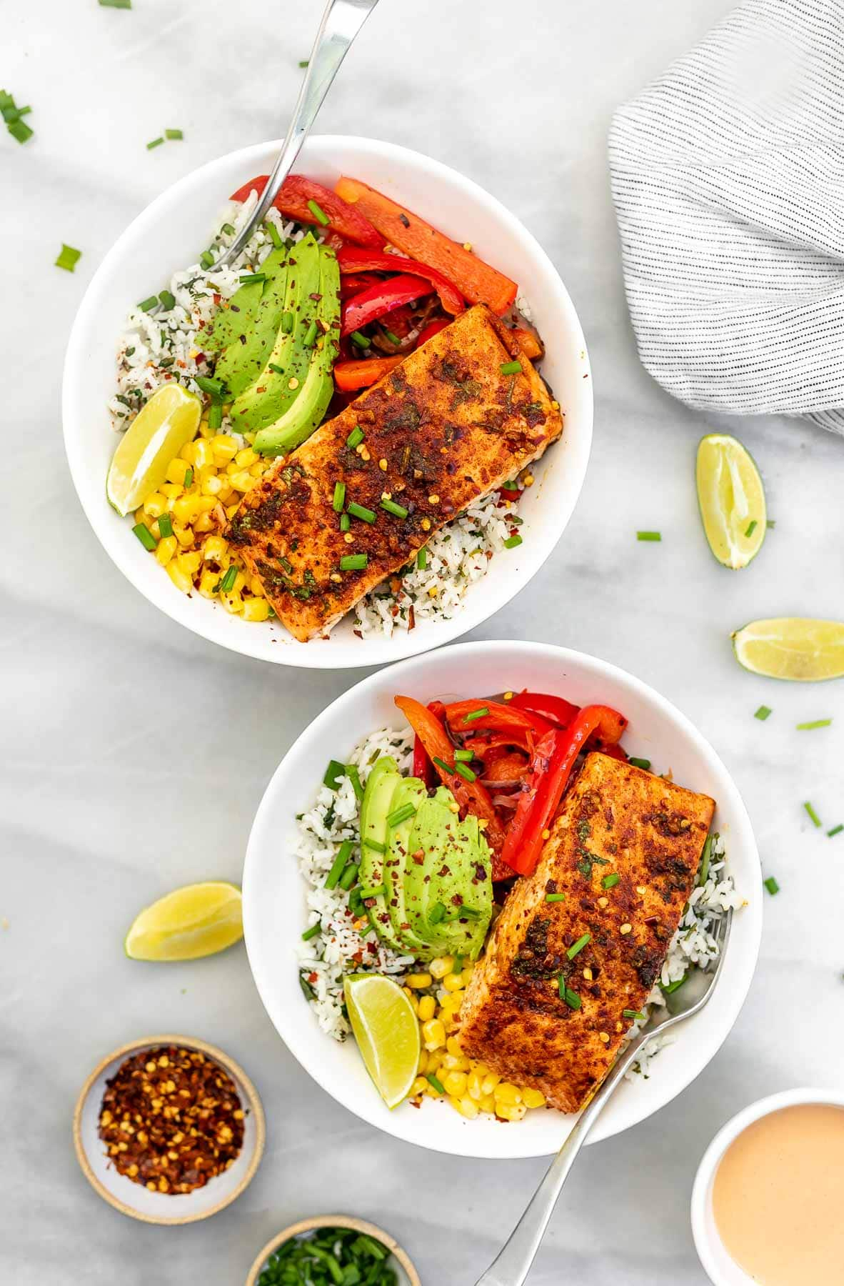 Two salmon bowls with forks on the side.