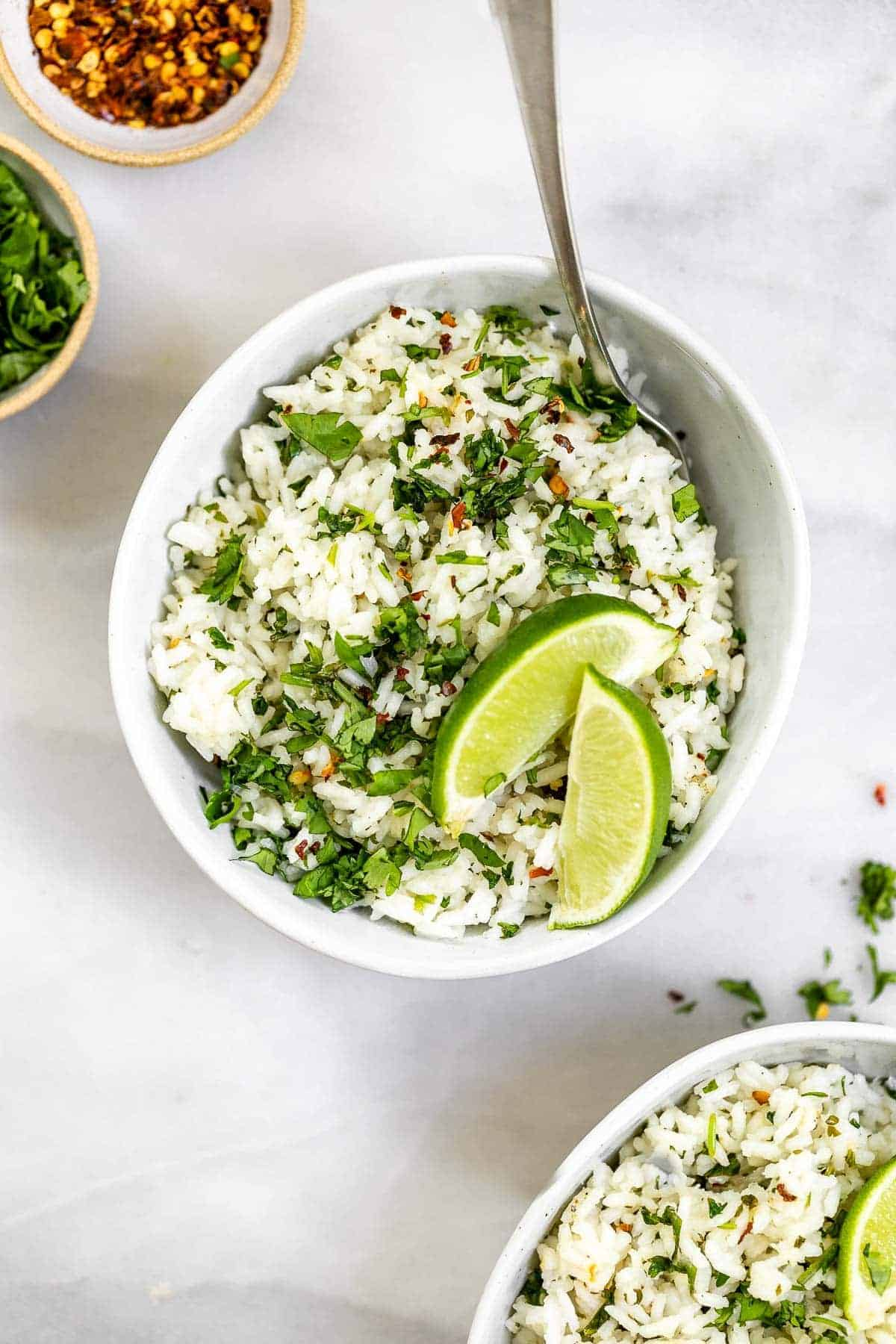 Two bowls of cilantro lime rice with lime wedges on top.