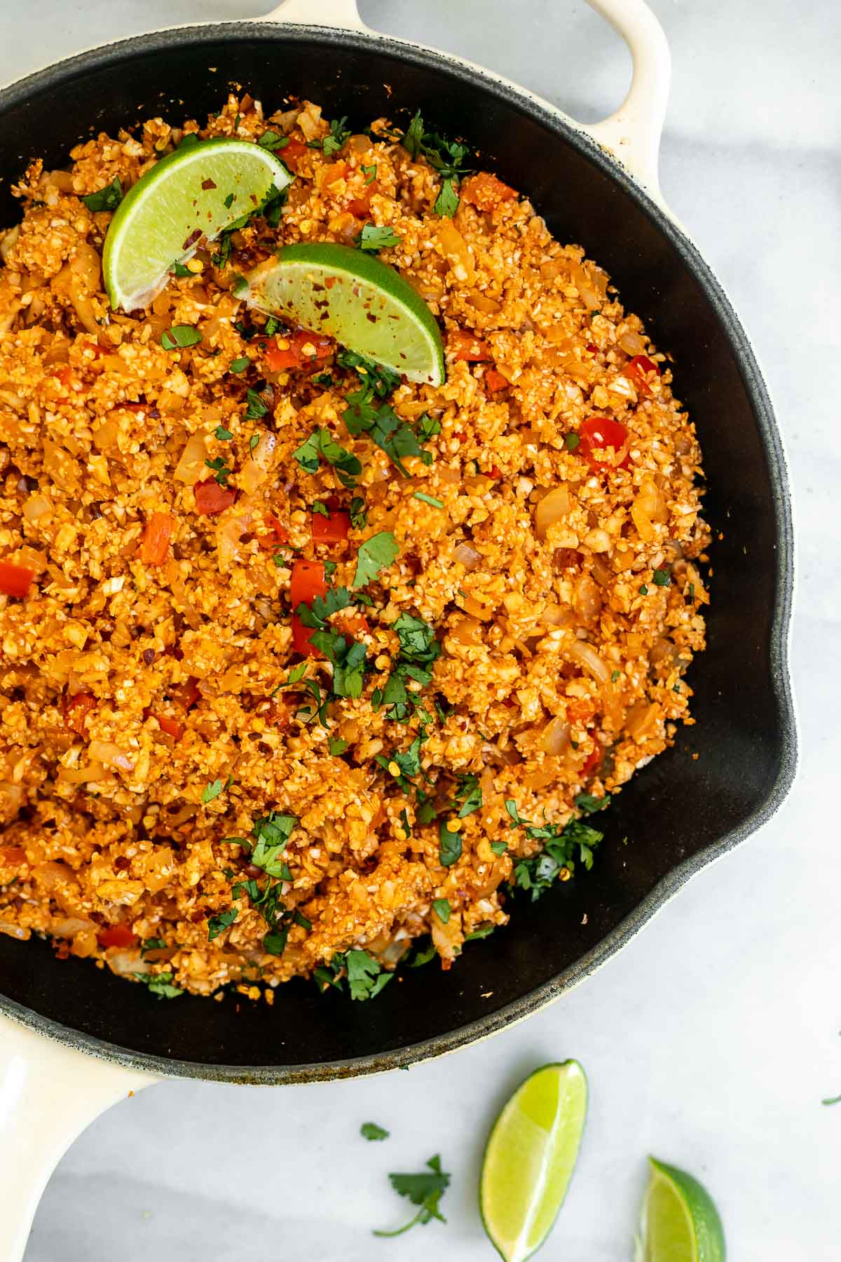 Up close image of the spanish cauliflower rice in a skillet to show texture.