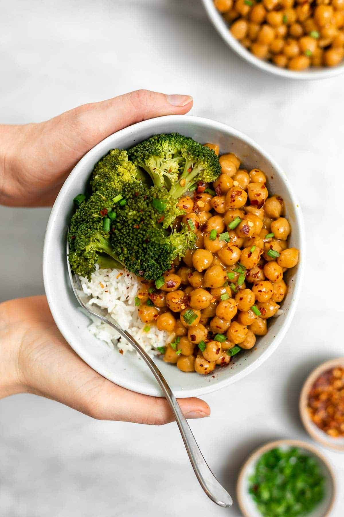 White rice with orange chickpeas and hands holding the bowl.