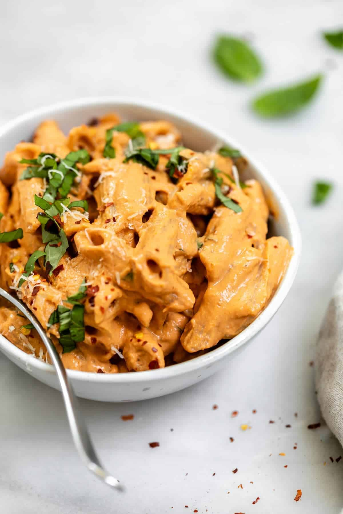 Tahini penne in a bowl with basil on top.