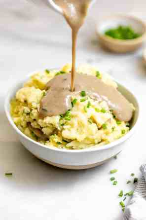Pouring gravy on top of mashed potatoes.