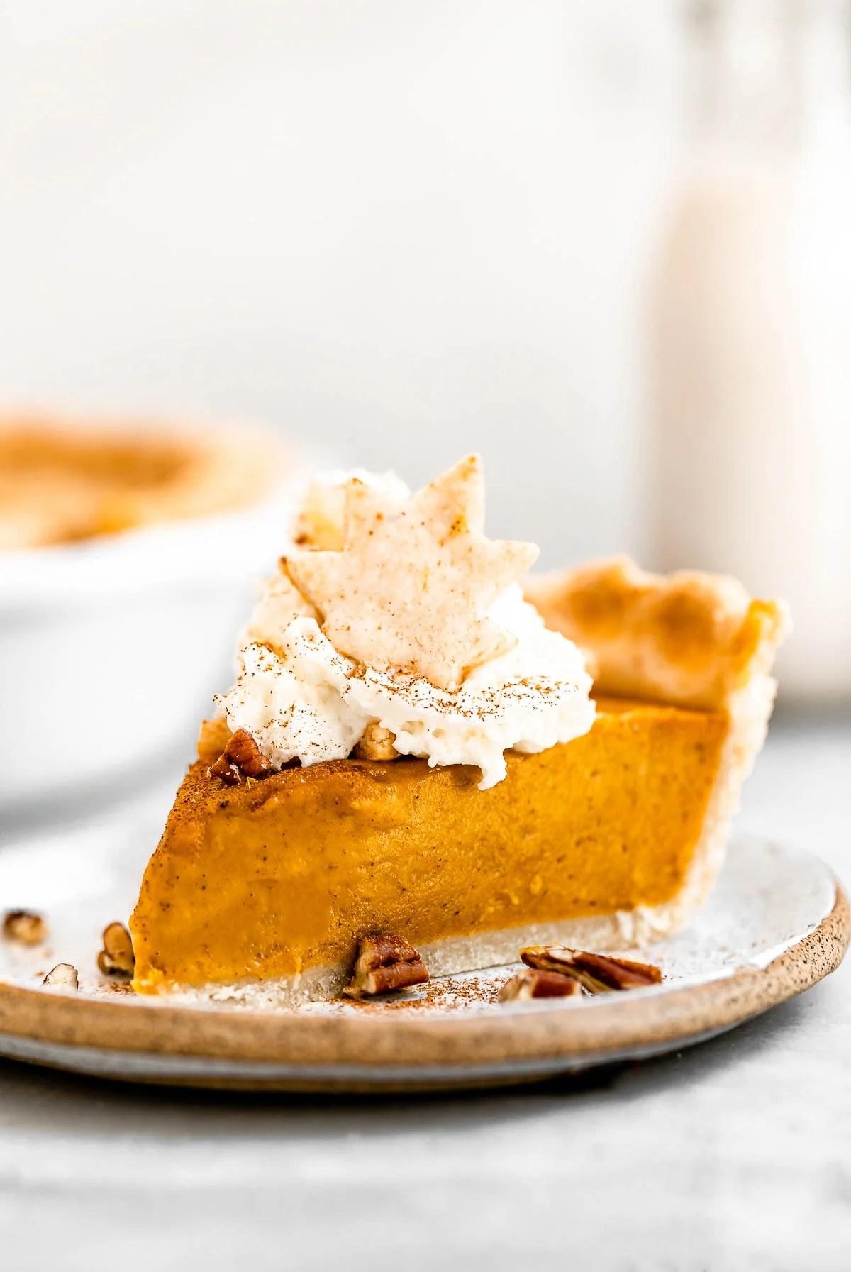 One slice of vegan pumpkin pie with pecans on top.