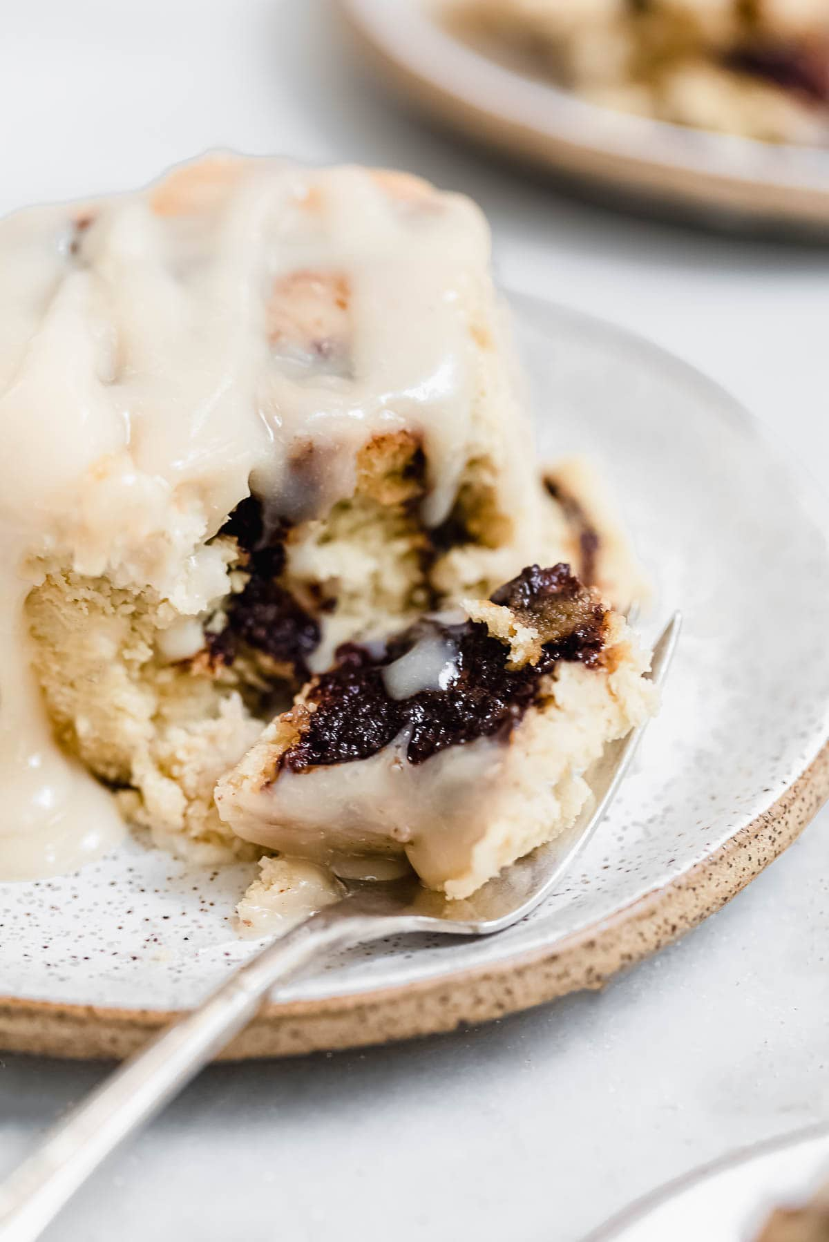 Up close image of the gluten free vegan cinnamon roll with a fork.
