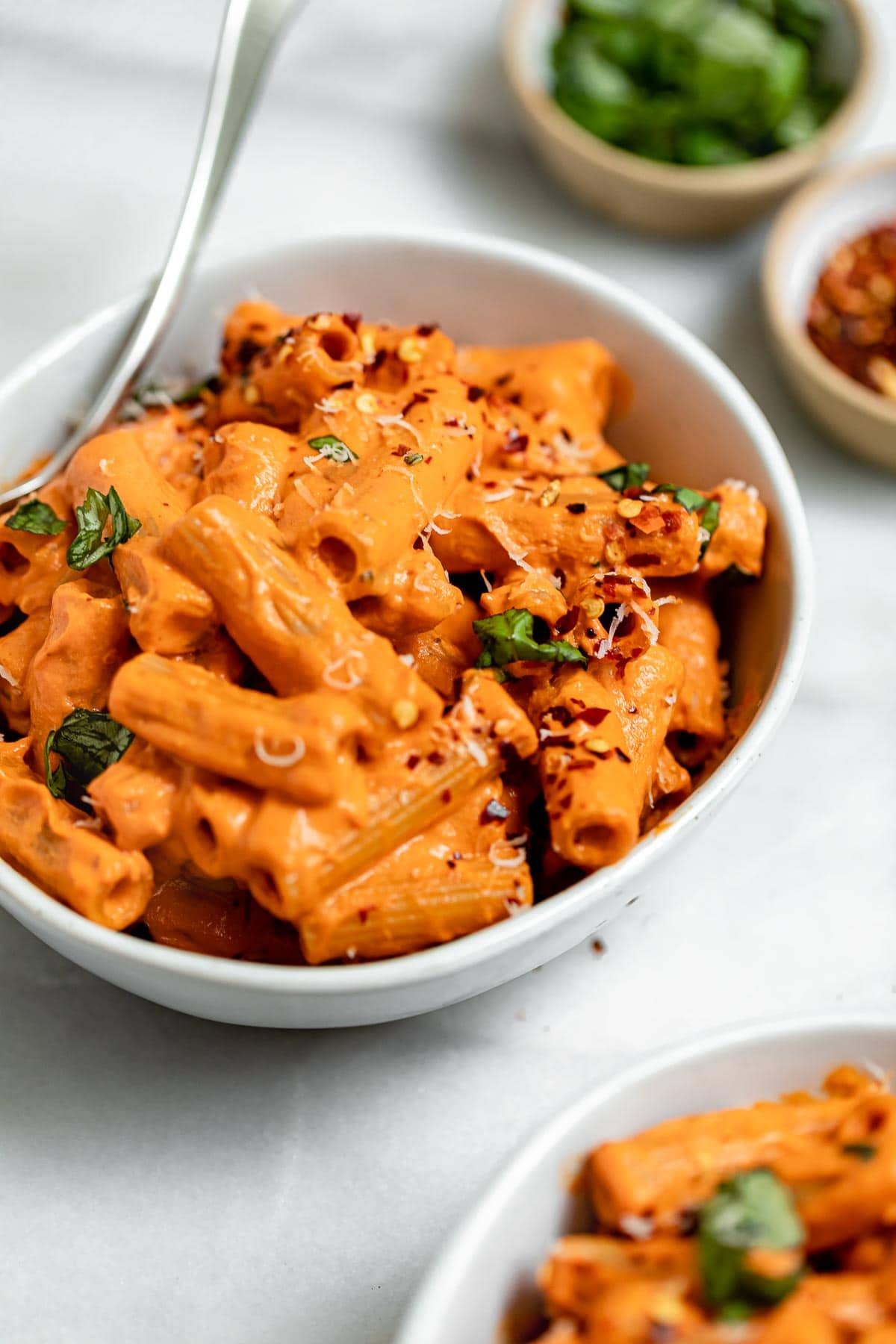 Angled view of the roasted red pepper pasta with basil on top.