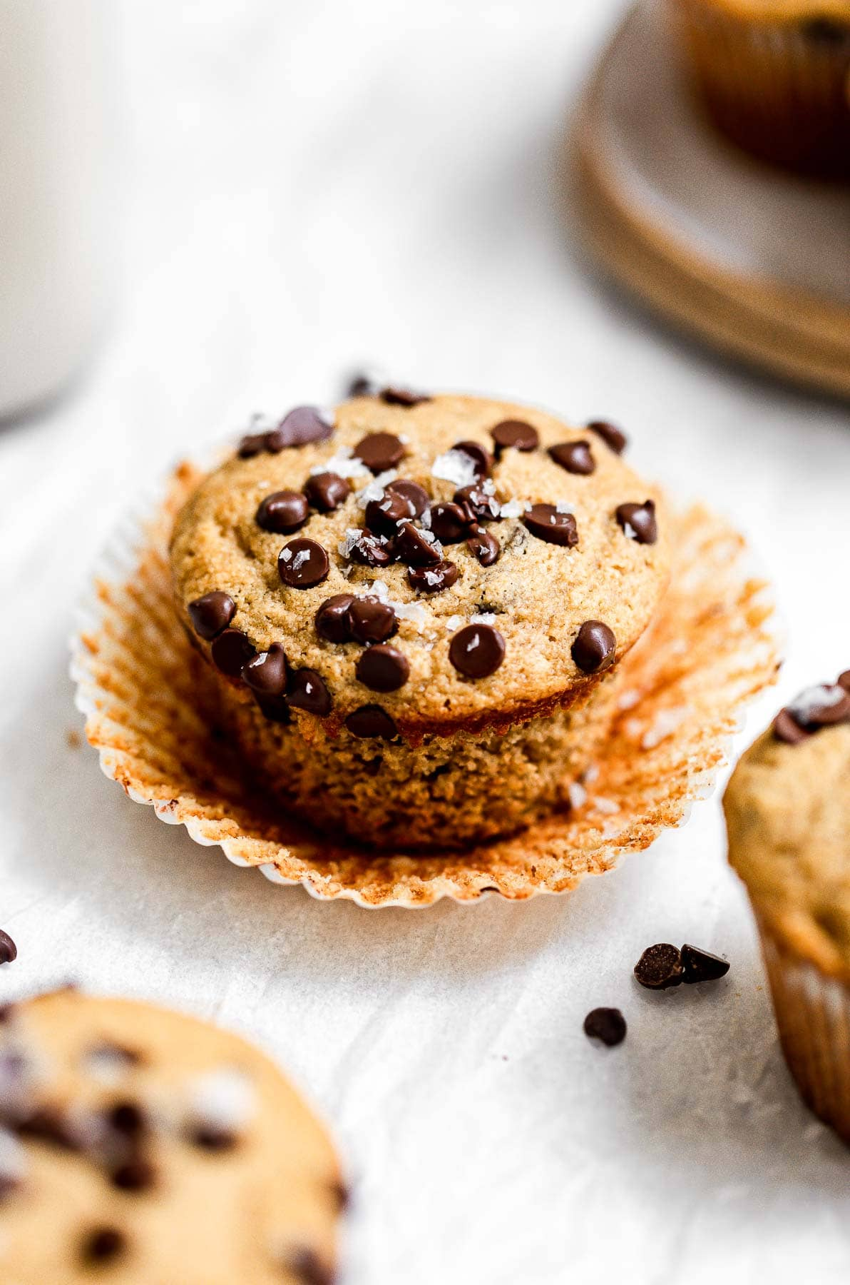 Banana muffin with chocolate chips on top and sea salt with the wrapper peeled off.