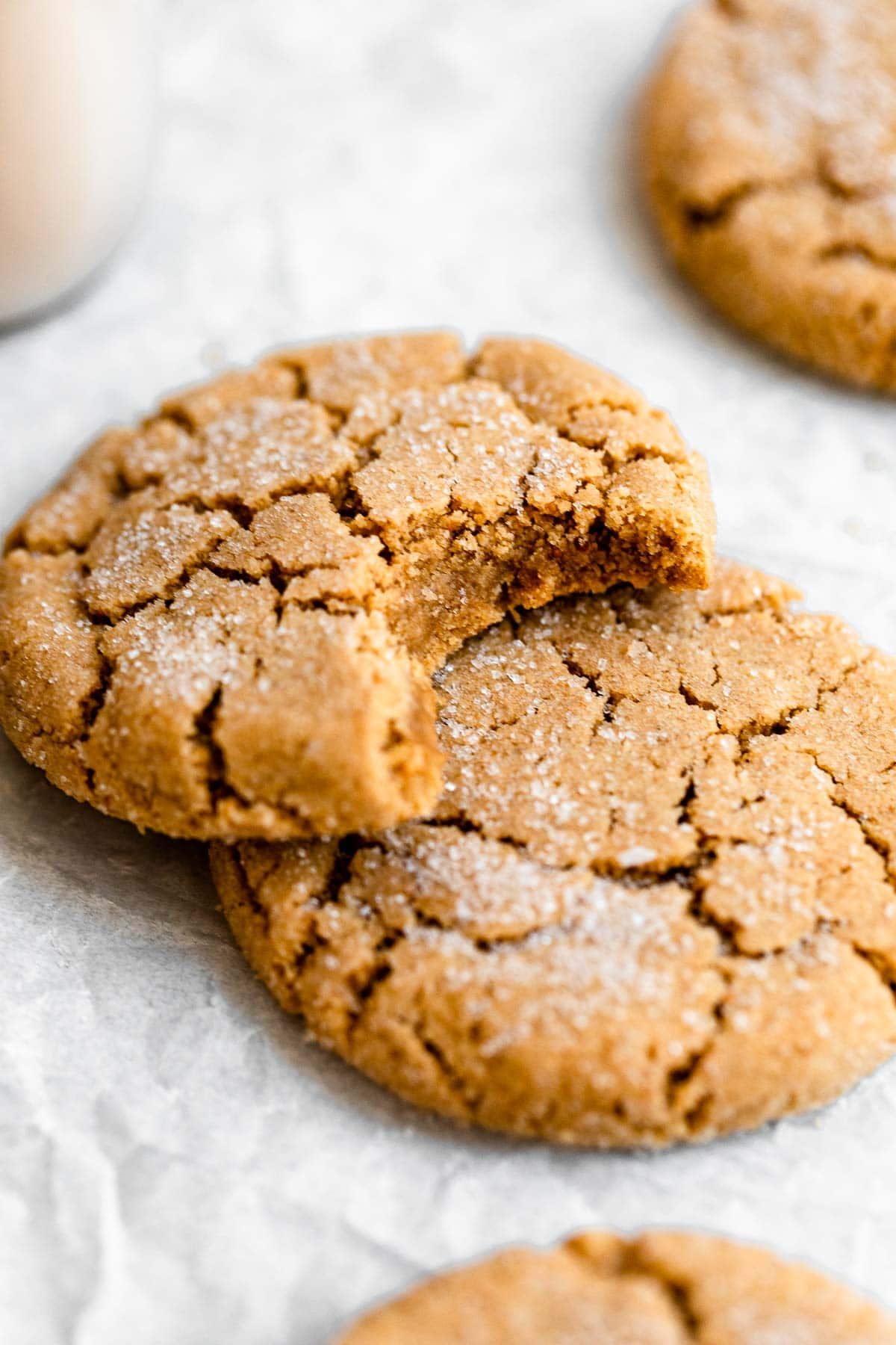 One vegan peanut butter cookie on the side with a bite taken out.