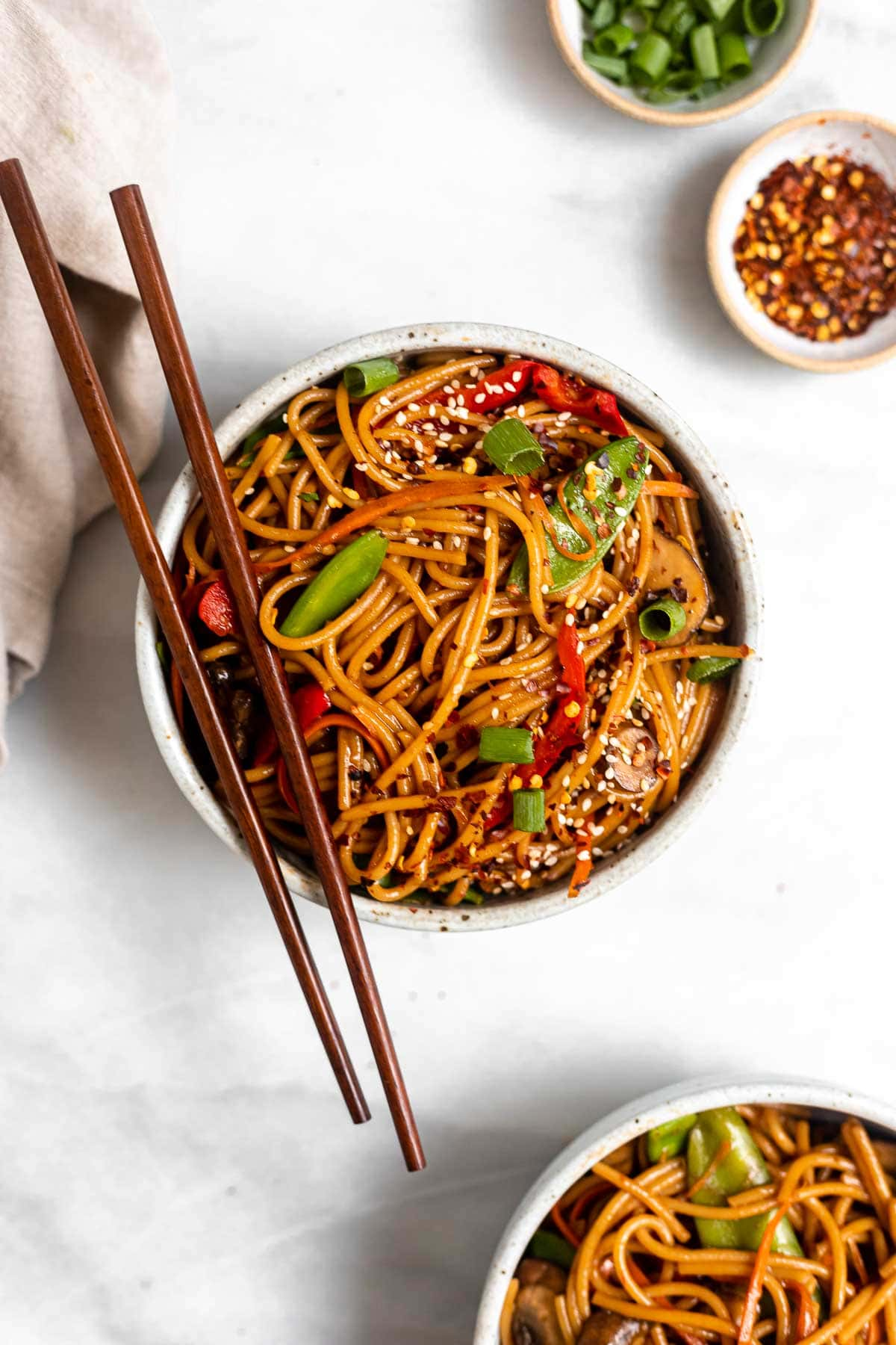 vegetable lo mein in a bowl with sesame seeds
