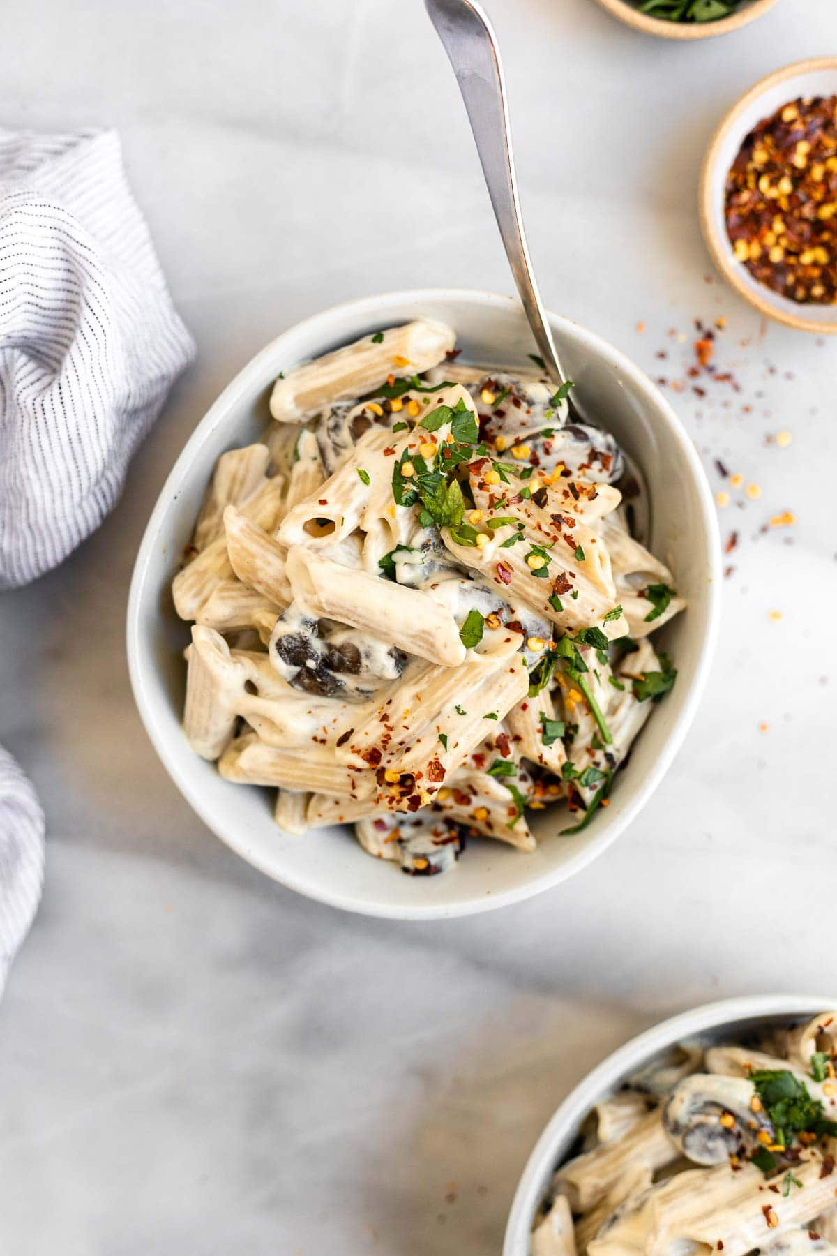 Two bowls of the cashew cream pasta with mushrooms and parsley.