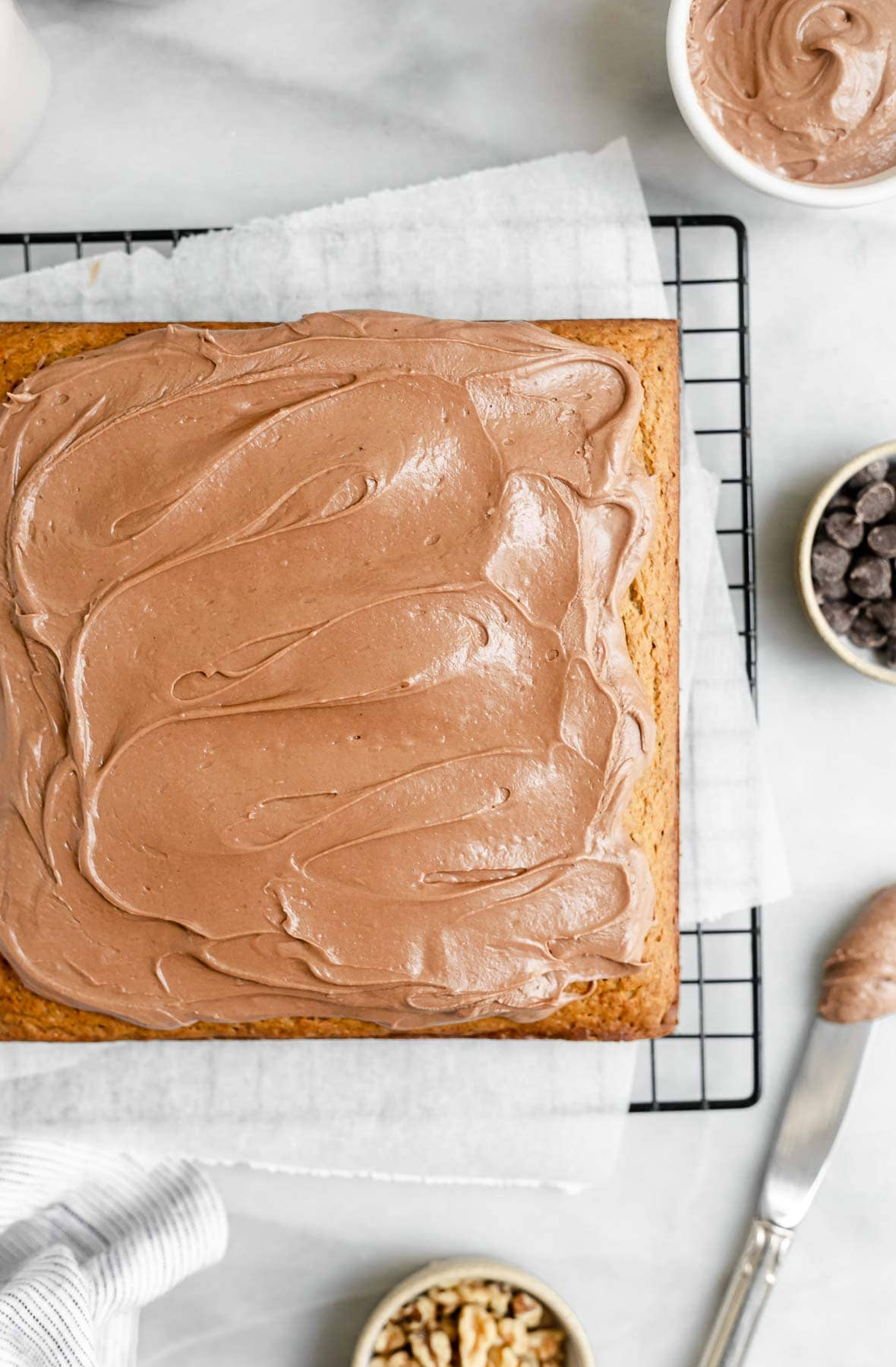 gluten free banana cake with chocolate frosting on parchment paper