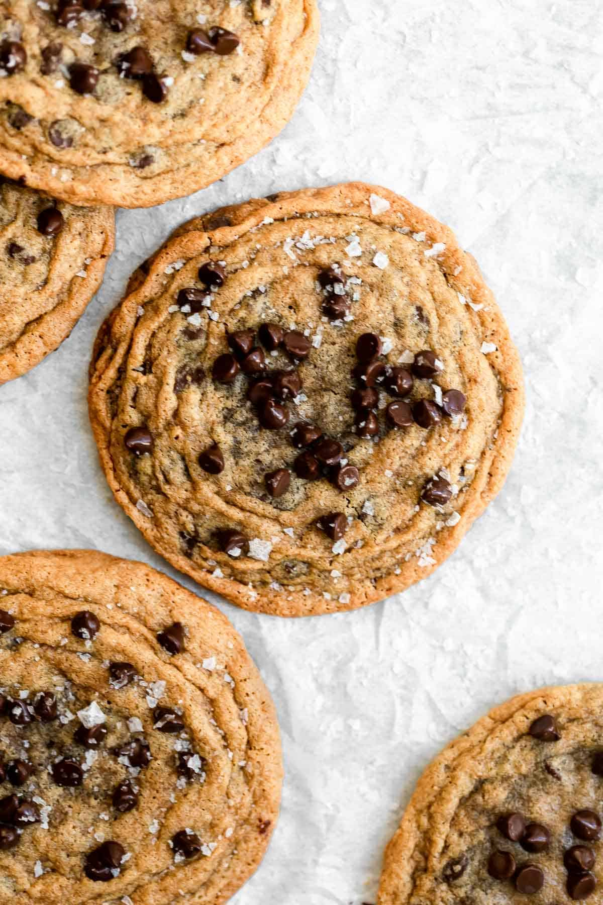 Overhead shot of cookies arranged on a white backdrop with chocolate sprinkled on top.