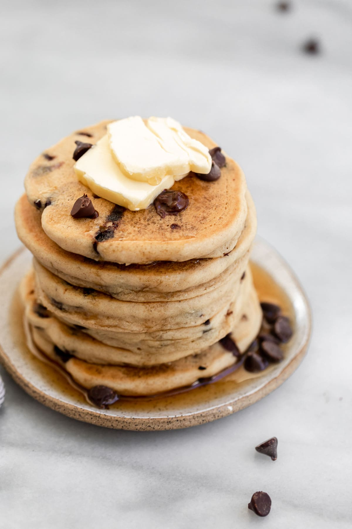 Tall stack of chocolate chip pancakes on a plate