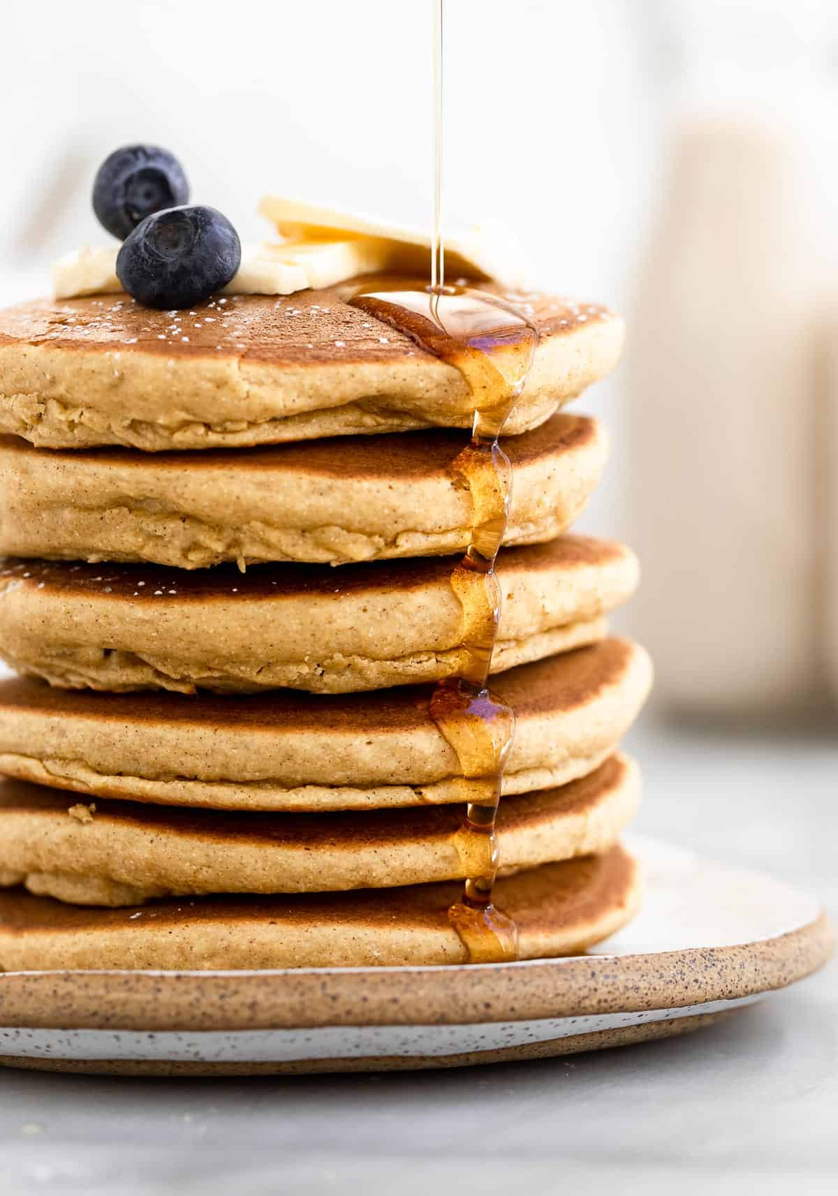 up close image of a stack of pancakes with maple syrup dripping down
