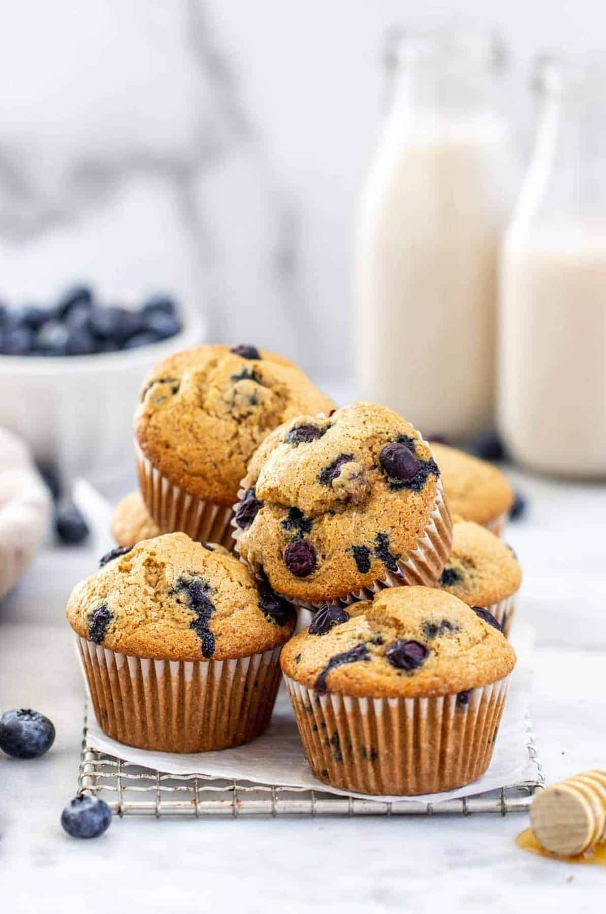 Gluten free blueberry muffins stacked with milk in the back.