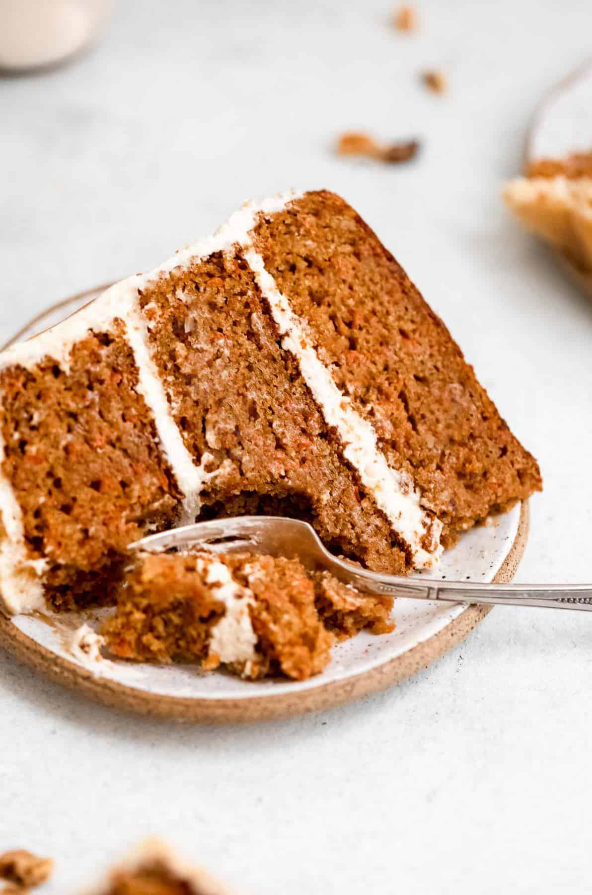 slice of gluten free carrot cake with a fork taking a bite