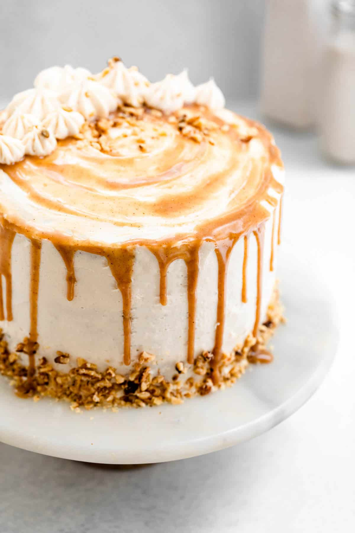 gluten free carrot cake with caramel drips on a marble cake stand
