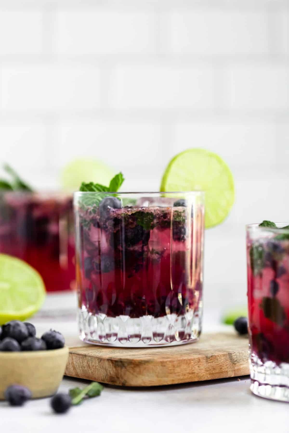 three glasses with blueberry mojito and lime wedges