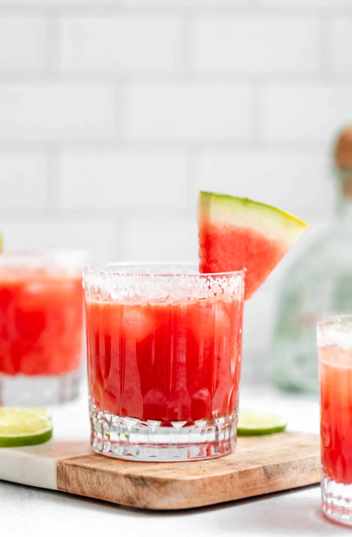 three watermelon margaritas in glasses with salted rims