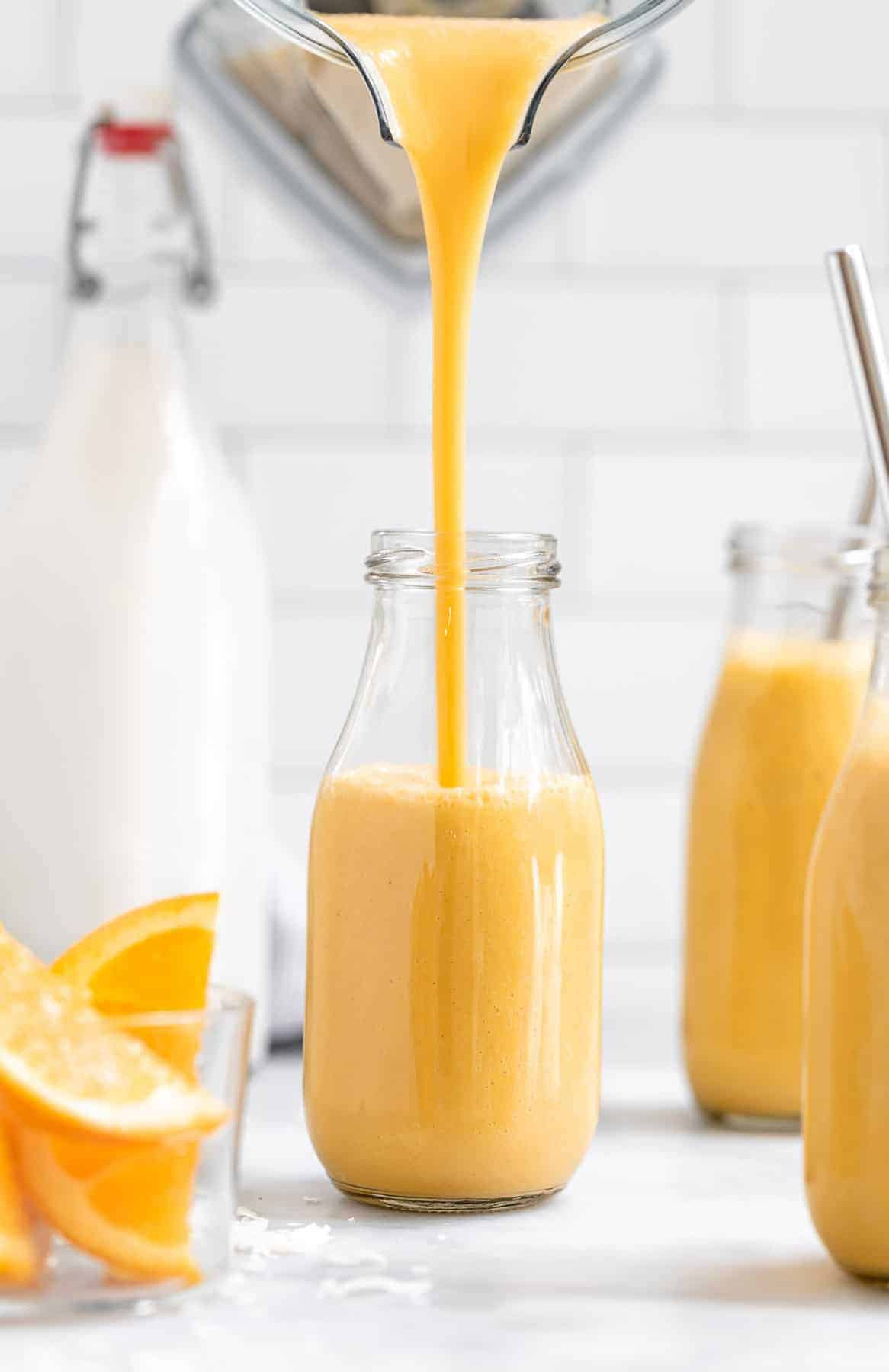 pouring the cantaloupe smoothie into a glass jar