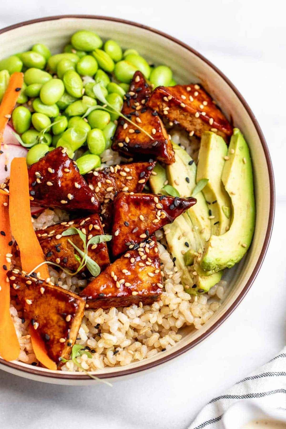 Vegan sushi bowl with tofu, avocado, and rice.