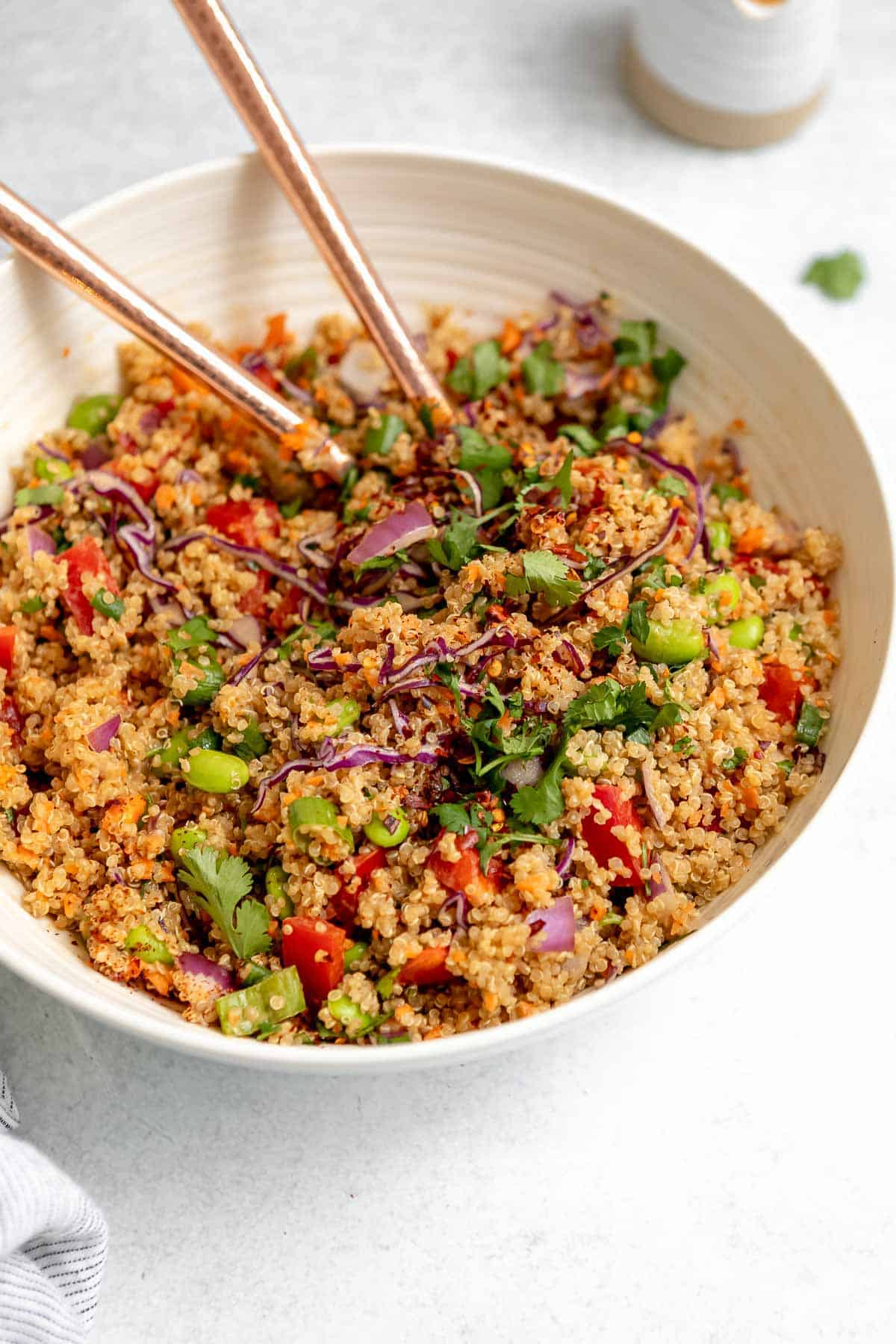 vegan quinoa salad with peanut sauce and vegetables in a white bowl