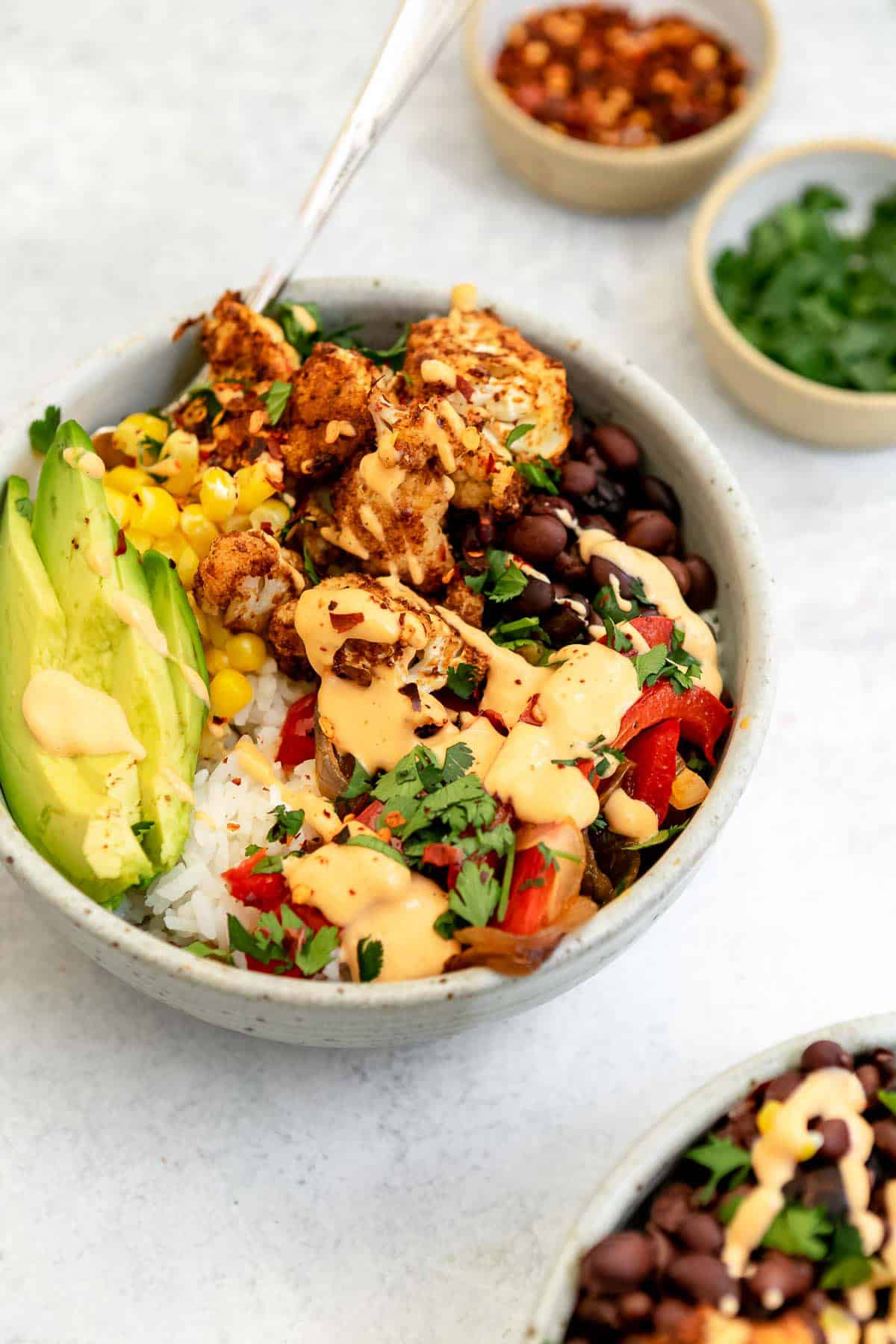 angled view of the vegan burrito bowl with bell peppers and roasted cauliflower