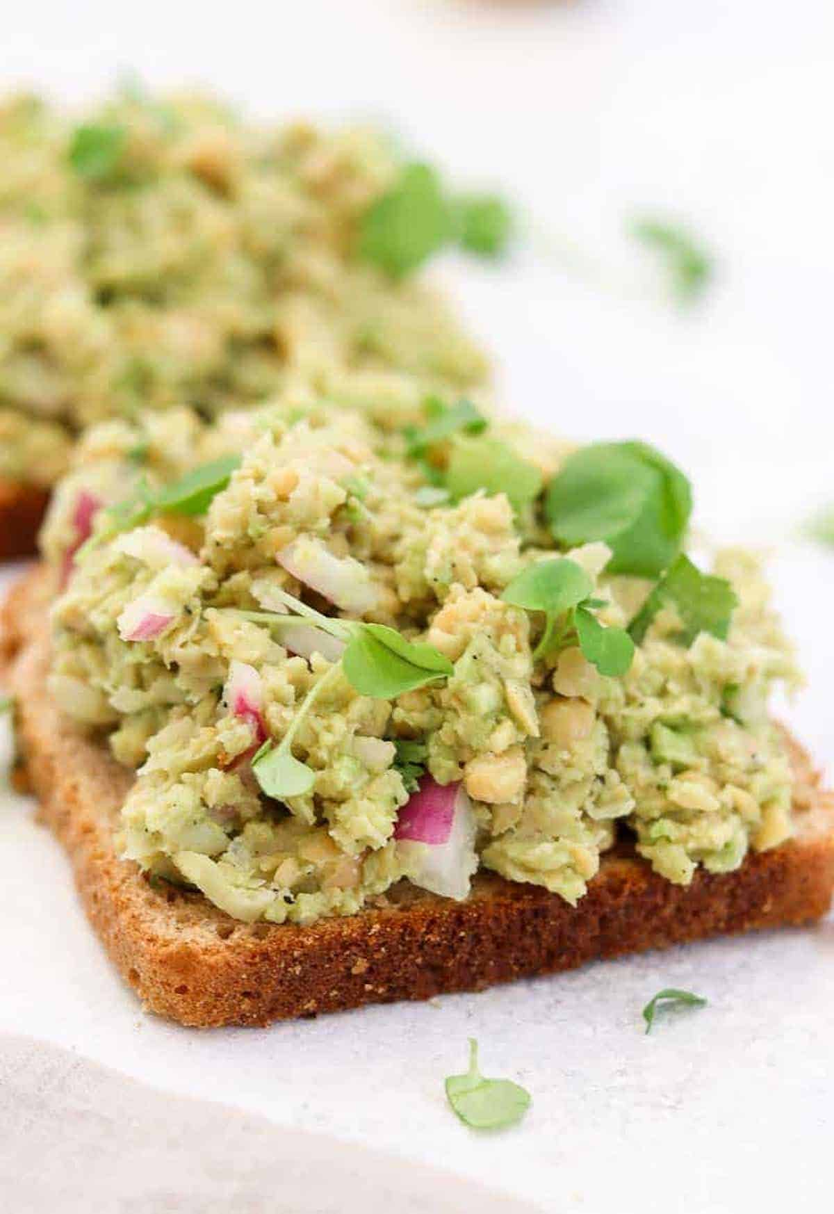 Chickpea salad on a piece of toasted bread.