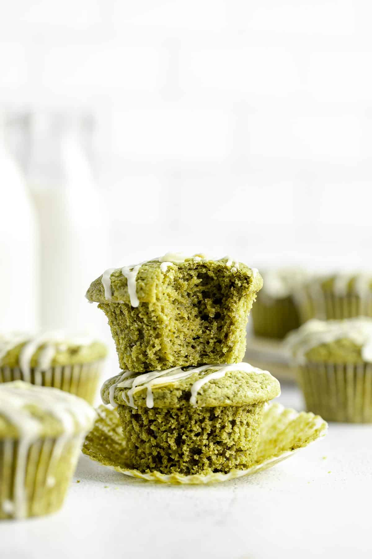 two matcha muffins stacked on each other with a bite taken out