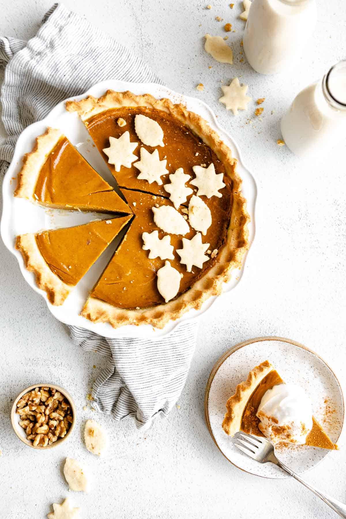vegan pumpkin pie in a pie plate with leaf cookies