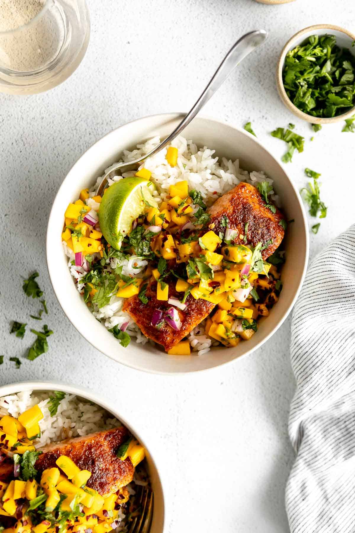 fish with mango salsa over rice in two white bowls