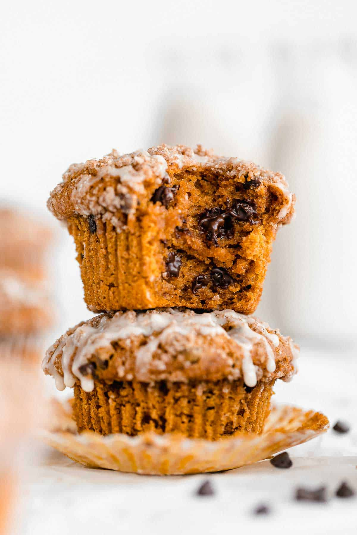 two gluten free pumpkin muffins stacked on each other with chocolate chips